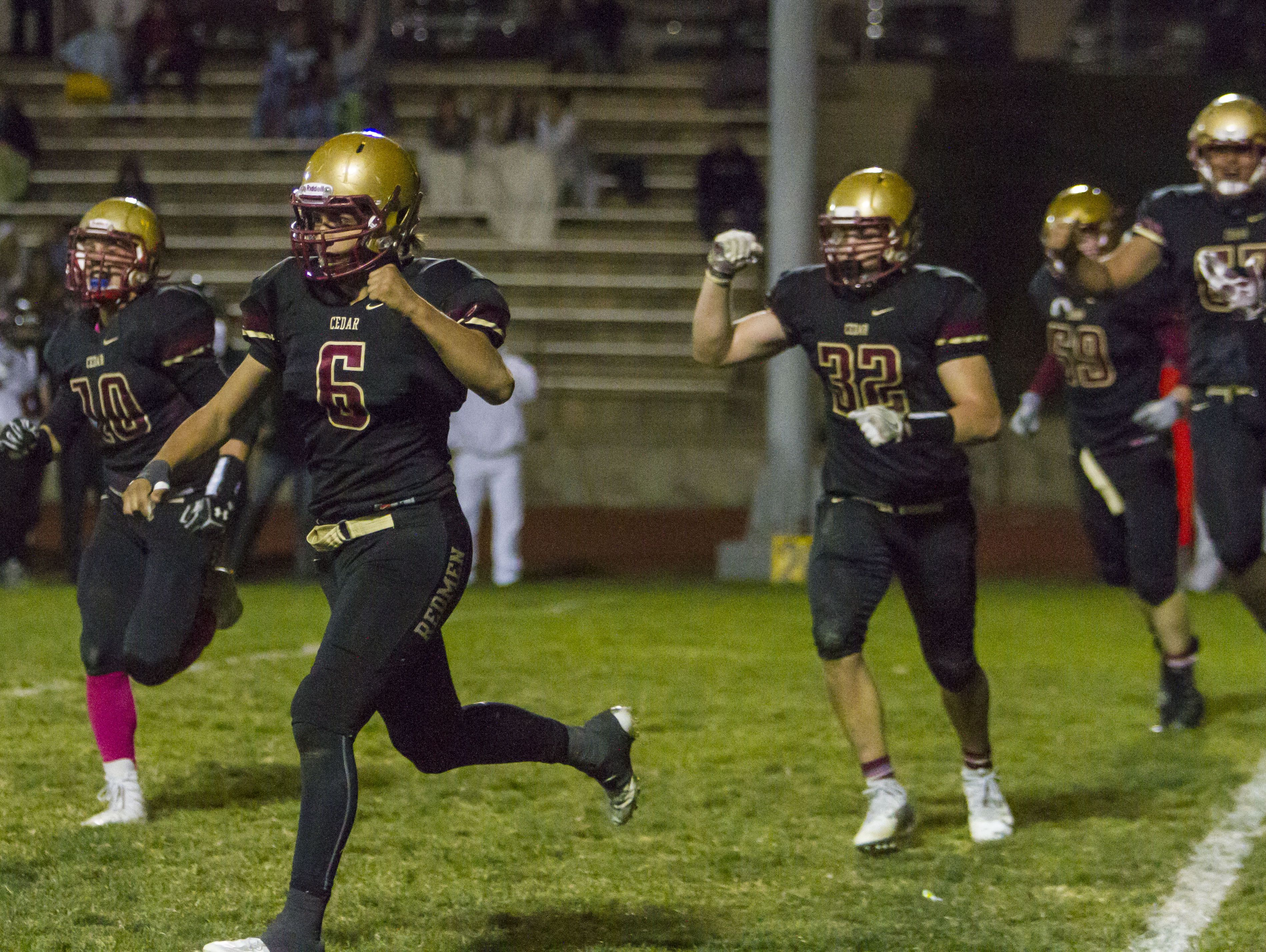 Cedar's defense celebrates getting a safety during the fourth quarter of Friday's game against Hurricane in Cedar City, Oct. 7, 2016.