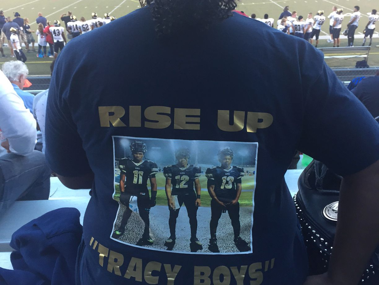 """Laverna Tracy is wearing a T-shirt that has three words on the back: """"Rise up Tracy boys!!!"""" Above those words is a picture of three Decatur Central players. No. 11, No. 12 and No. 13."""