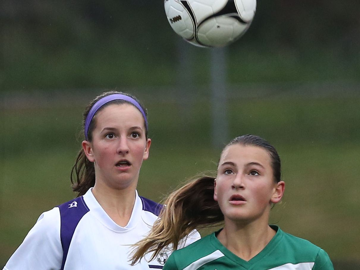 From left, John Jay's Erin Walsh (10) and Brewster's Danielle Regan (14) battle for ball control during a soccer game at John Jay High School in Cross River Oct. 13, 2016. John Jay won the game 6-0.