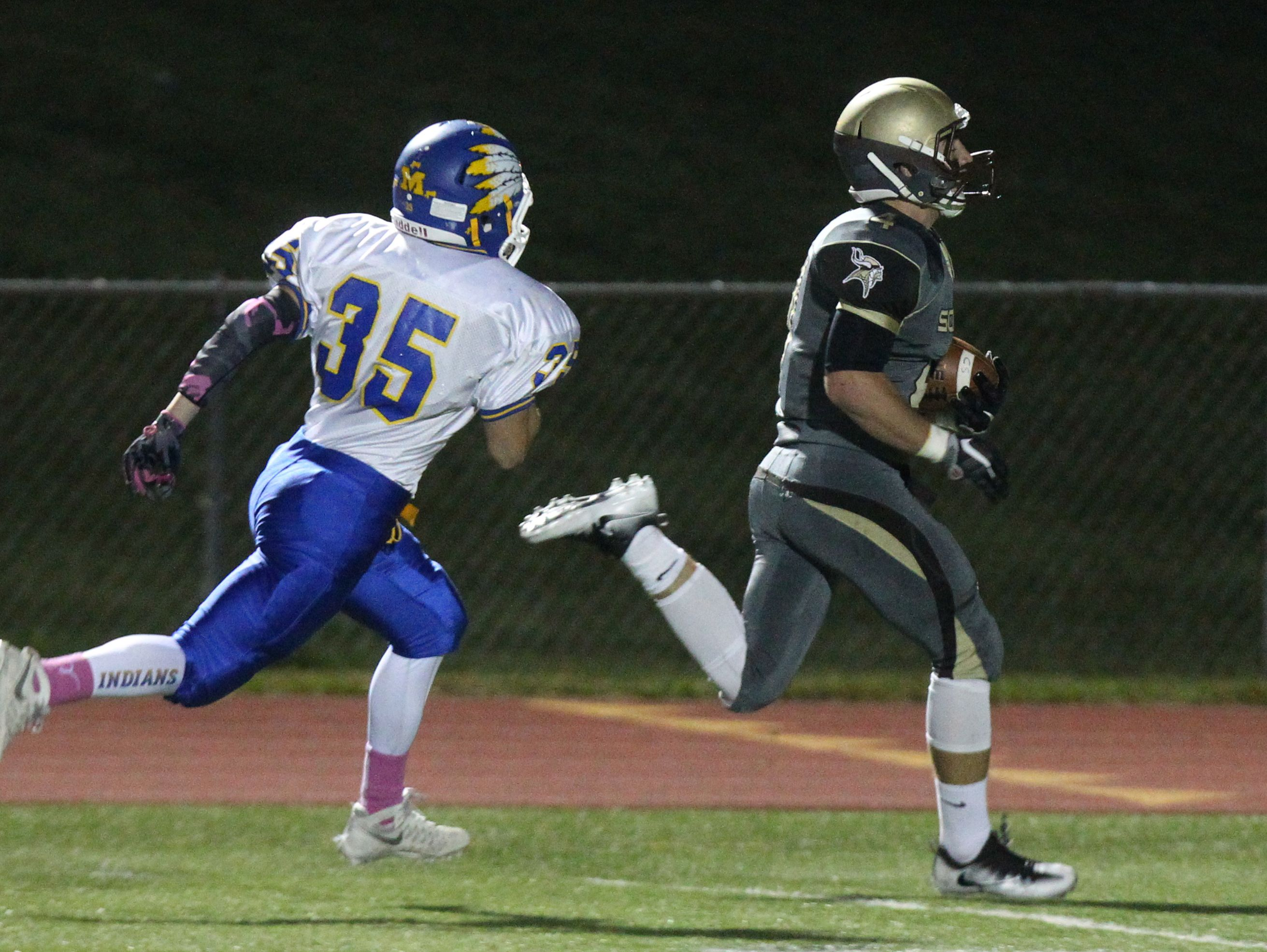Clarkstown South's Kyle Samuels runs for a touchdown as Mahopac's Anthony Ocello pursues during their Class AA playoff game at Clarkstown South Oct. 14, 2016.