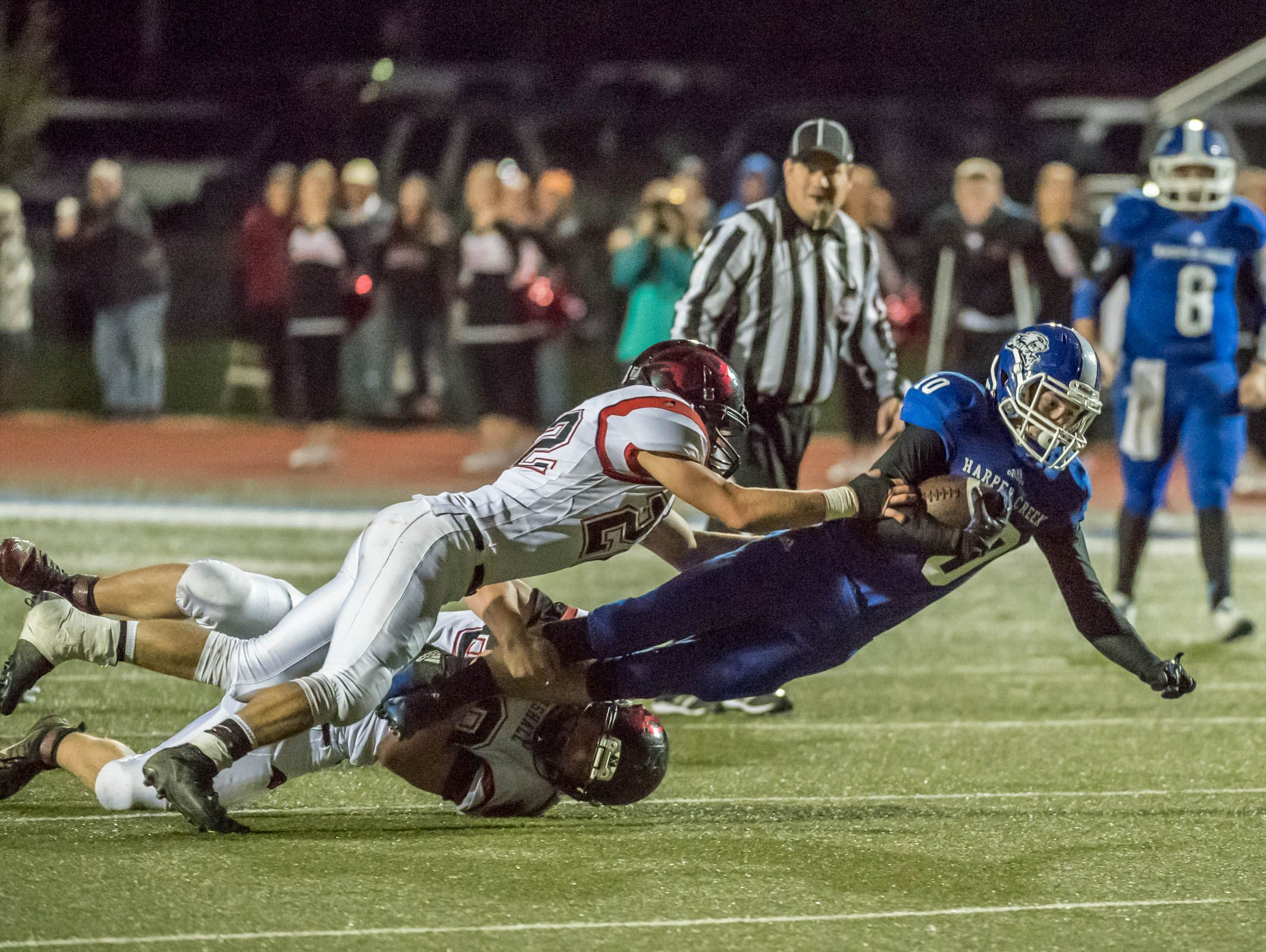 Harper Creek's Dawson Bartlett (10) gets brought down by Marshall tackles during first half action Friday evening,