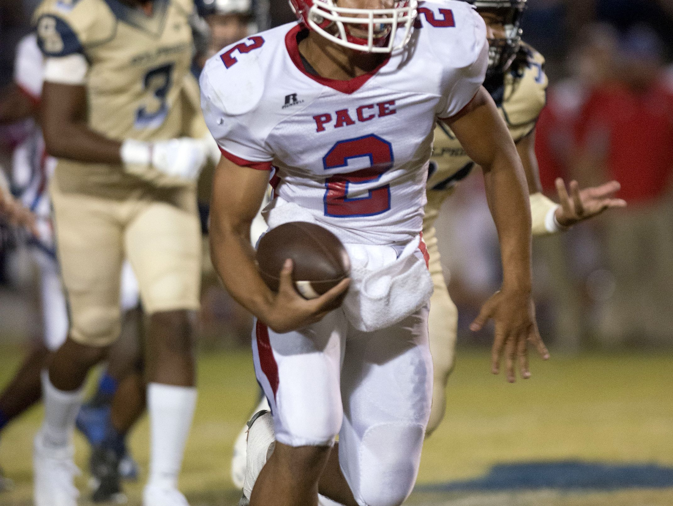 Pace quarterback, Damean Bivins, (No. 2) looks for a hole in the line of scrimmage after being forced out of the pocket by the Gulf Breeze defense during Friday night's District-2 6A game.