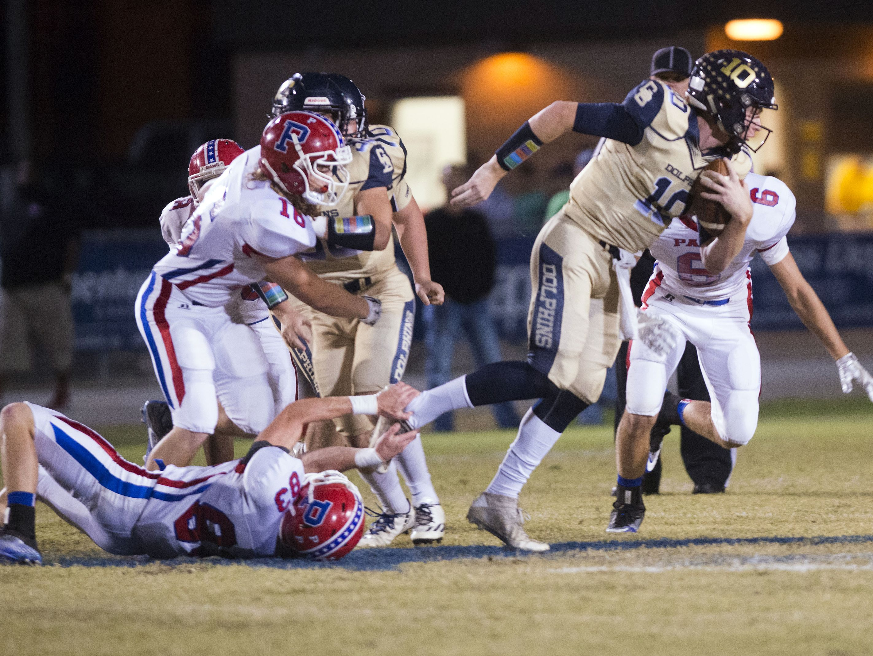 Gulf Breeze quarterback, Tyler Phelps, (No. 10) slips out of the clutches of the Pace defense during Friday night's District-2 6A game.