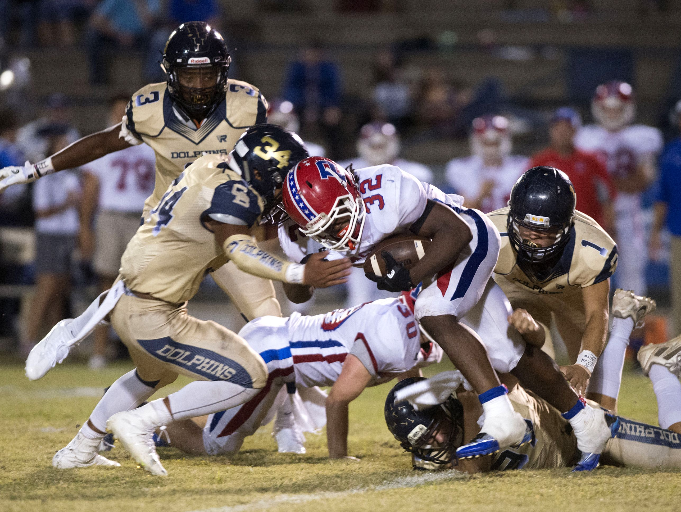The Gulf Breeze High defense shuts down Pace High School running back, Anthony Johnson, Jr., (No. 32) during Friday night's District-2 6A game.
