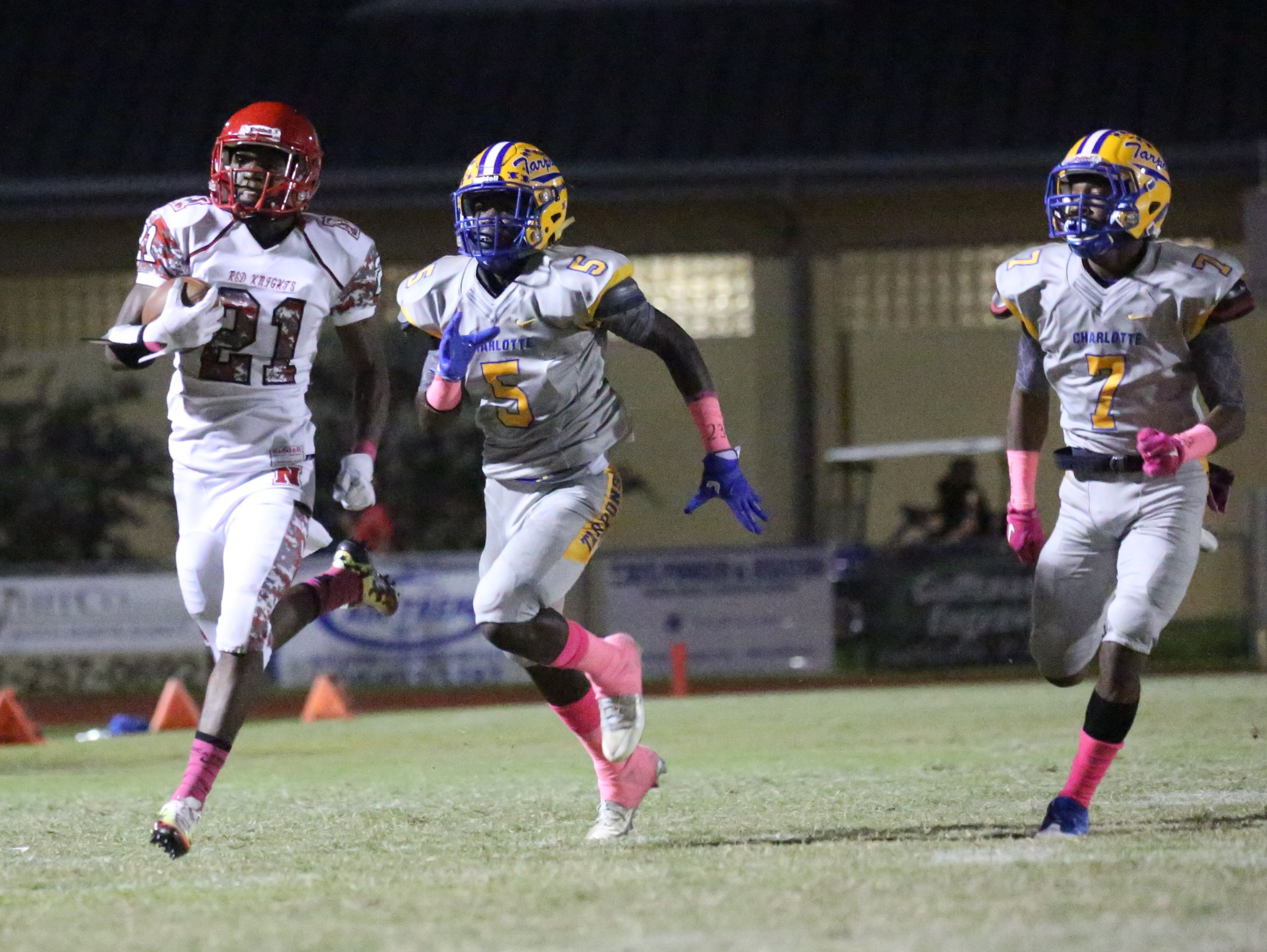 Charlotte defenders, Savorion Warren and Ny Harvey try to catch North Fort Myers' Terry Lindsey as he gains yards as North Fort Myers played at Charlotte Friday night.