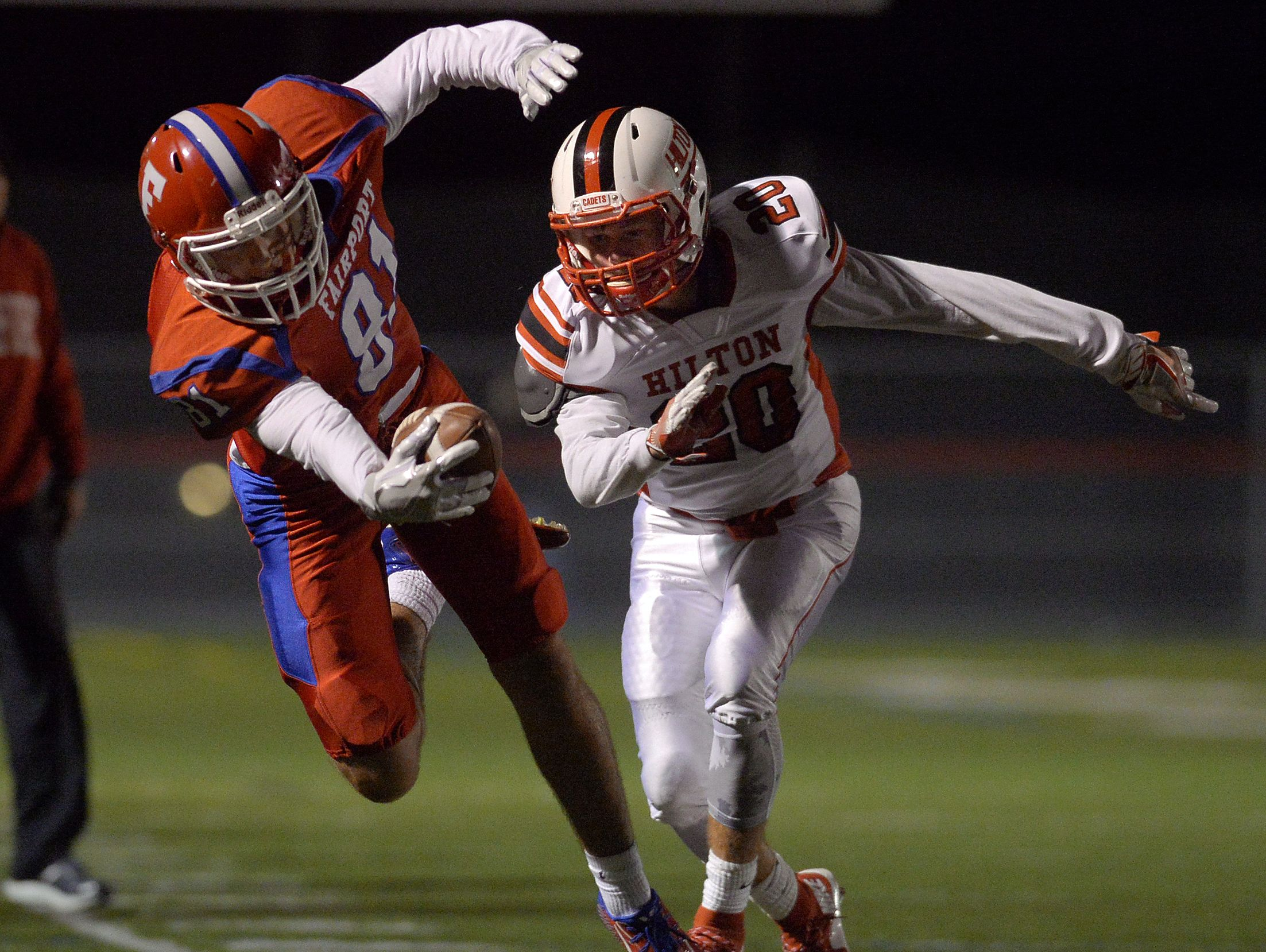 Fairport's Steve Gable reaches for extra yards after being pushed out of bounds by Hilton's Tyler Dalle a during regular season game at Fairport High School on Oct. 14, 2016.