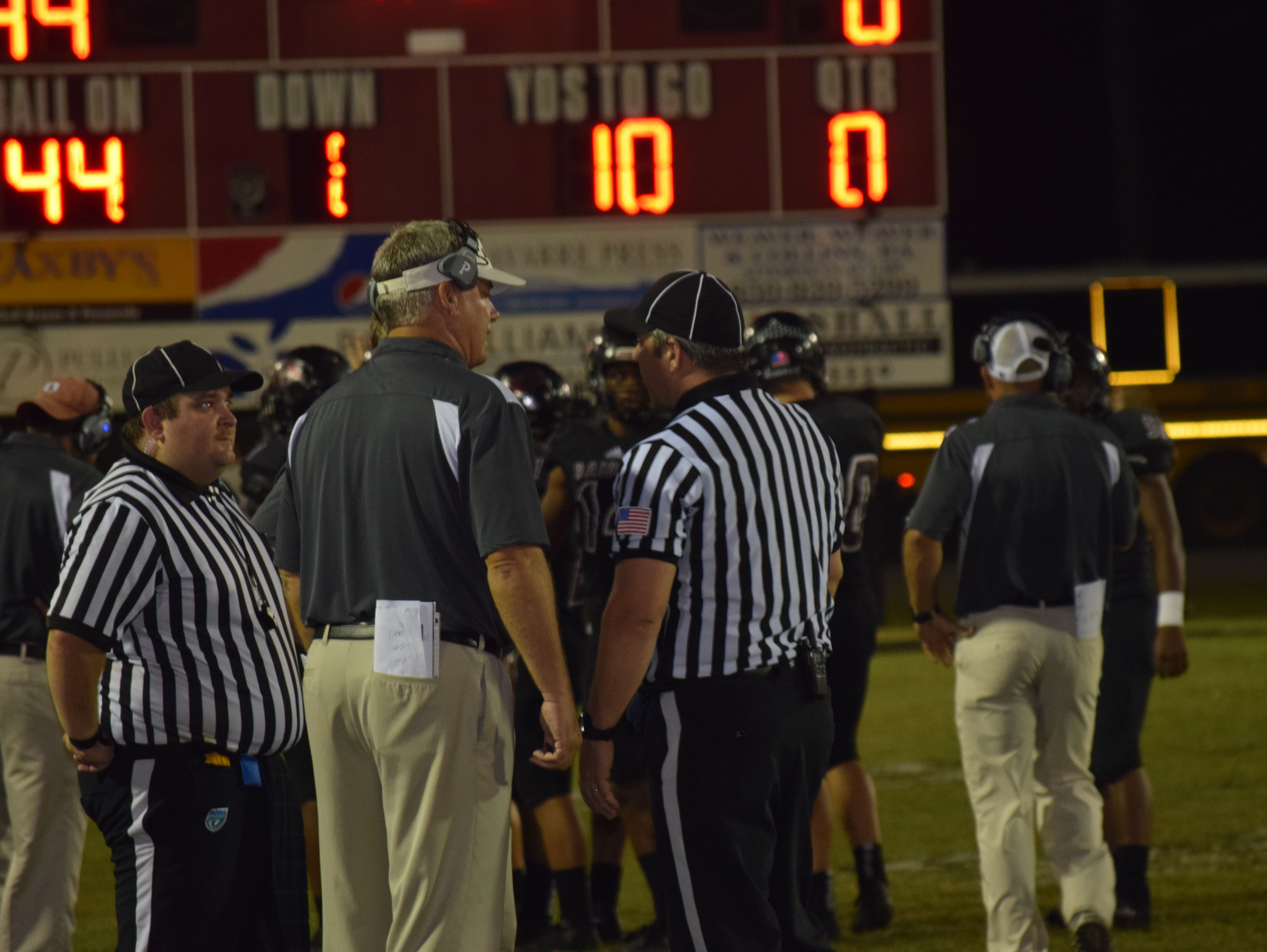Navarre coach Jay Walls confers with officials after the Raiders' final touchdown Friday night in a 44-0 win against Milton.