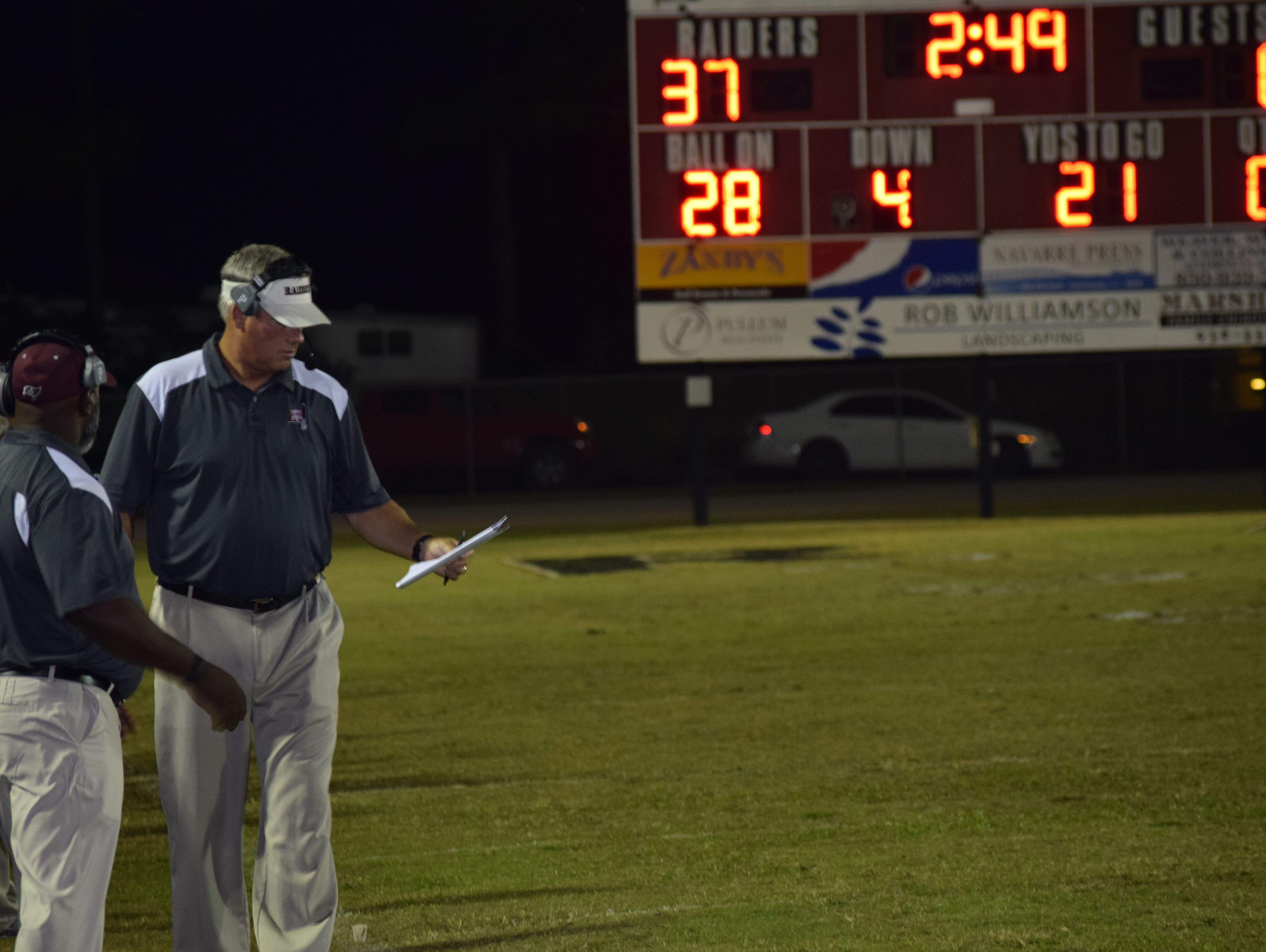 Navarre coach Jay Walls checks his playsheet in the third quarter of the Raiders' 44-0 win against Milton.
