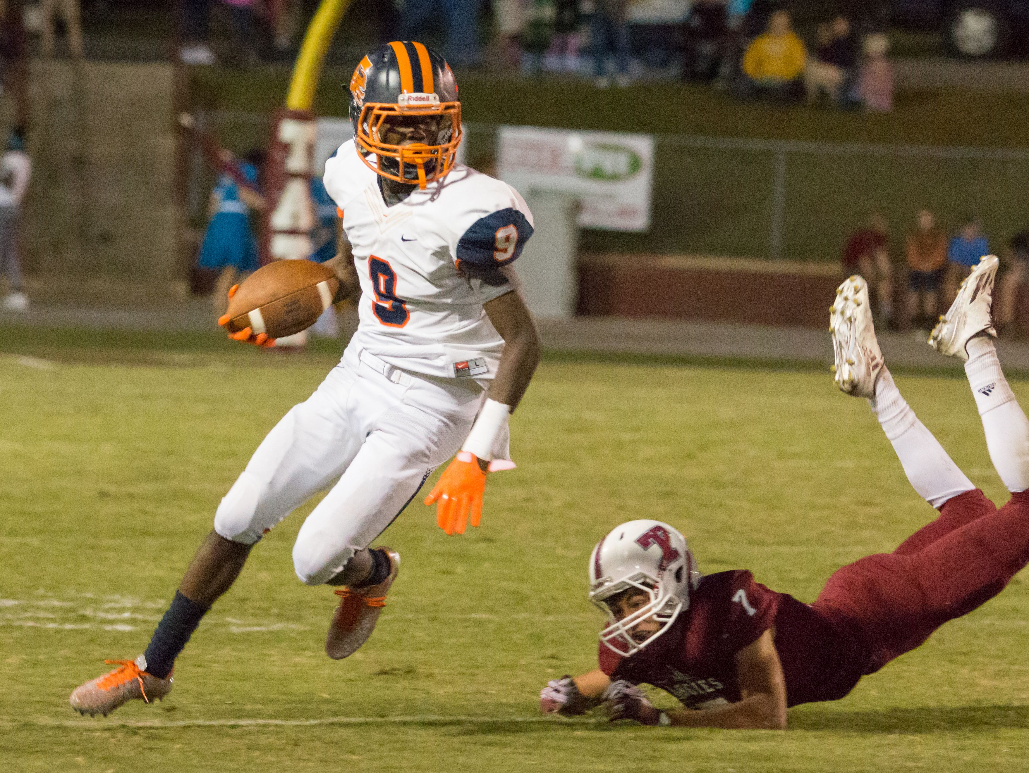 Escambia running back Ladarius Harris (9) gets past Tate's Patrick Palmer (7) after making him miss the tackle Friday night at Tate High School.