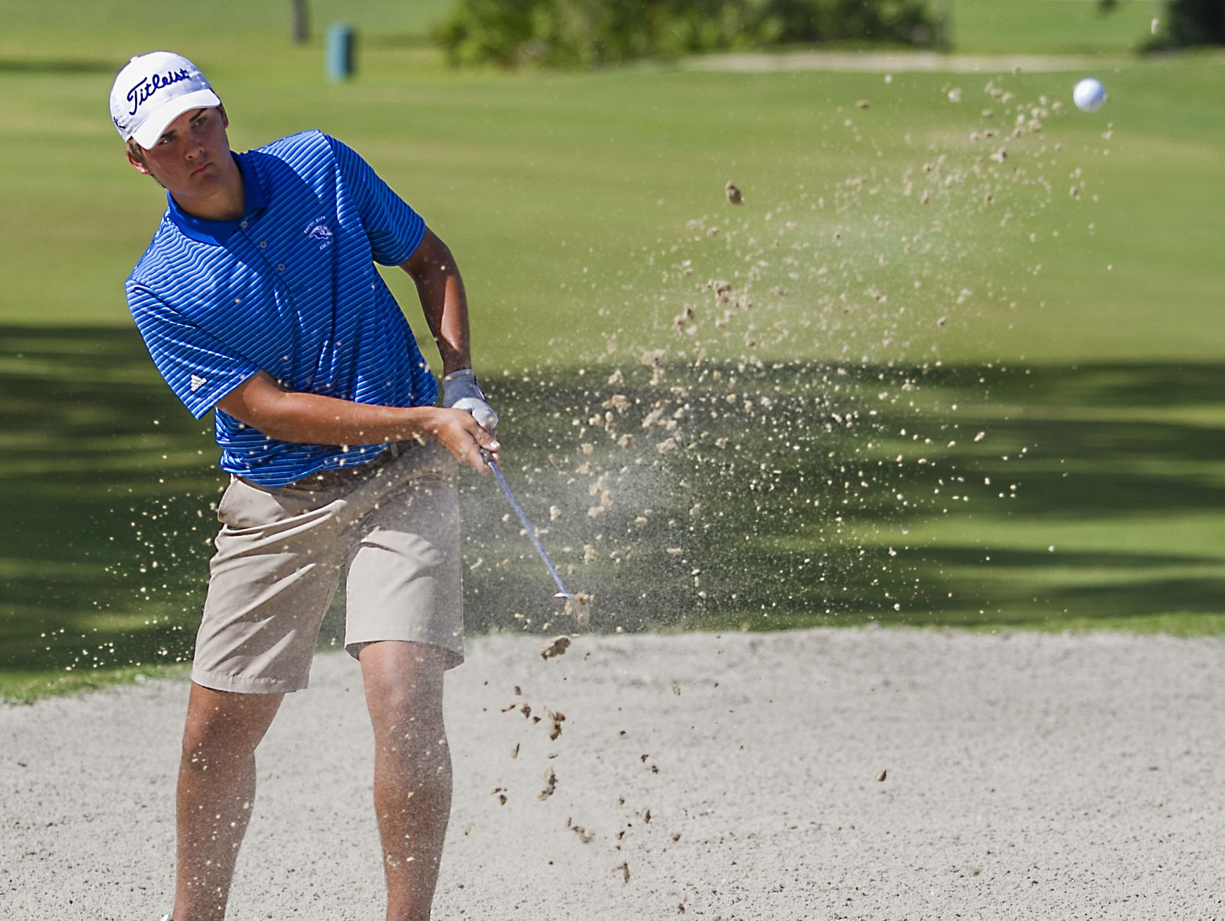 Adrian Strey, a member of the Ida Baker High School golf team, chips out of a sand trap while playing in the FHSAA class 2A Region 7 tournament Monday morning at Palmetto-Pine Country Club in Cape Coral.