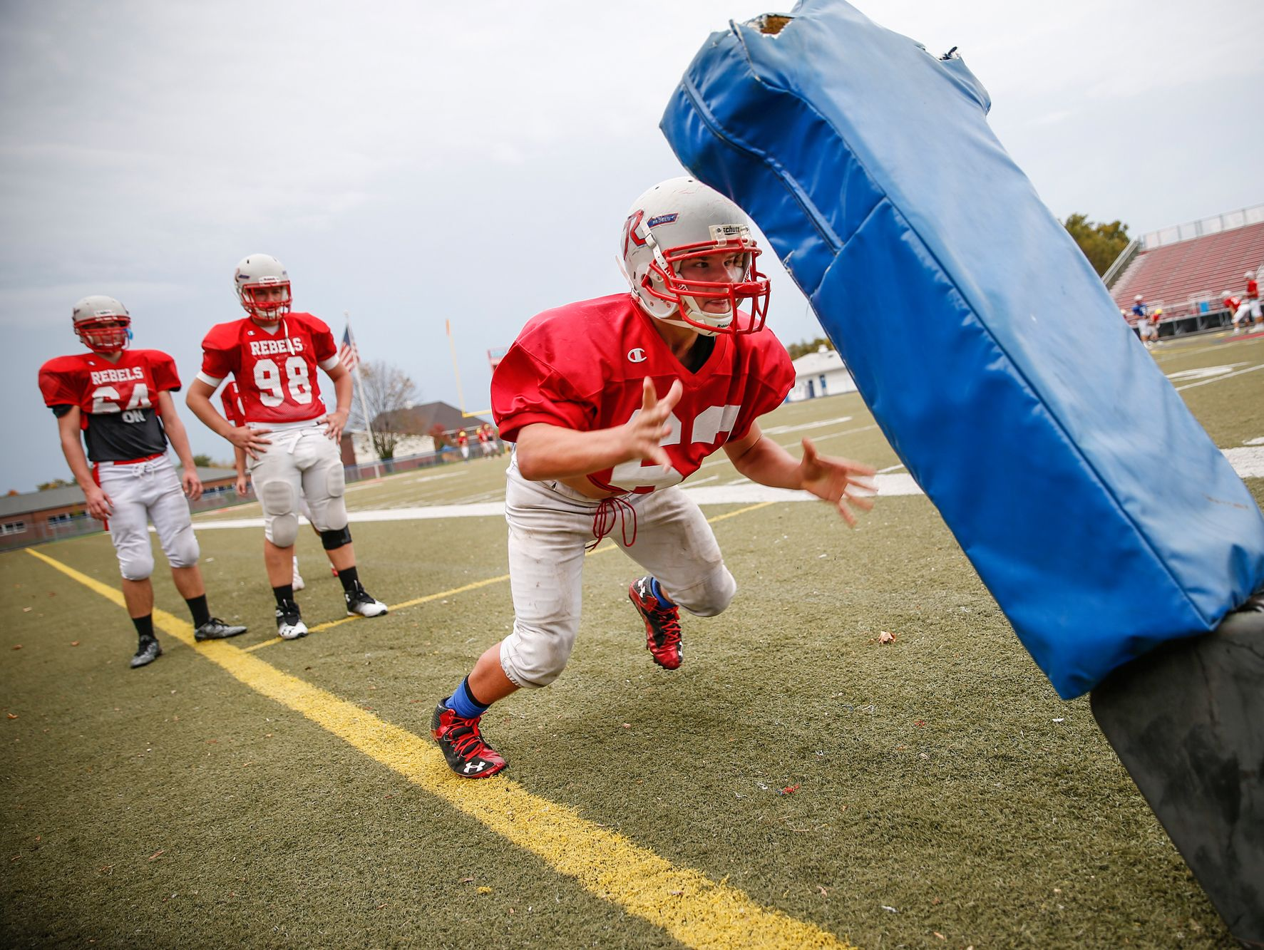 Roncalli Rebels nose tackle Max Quebe, a 5-foot-2-inch, 135-pound Russian adoptee, works to drive back a sled during practice on Oct. 19, 2016.