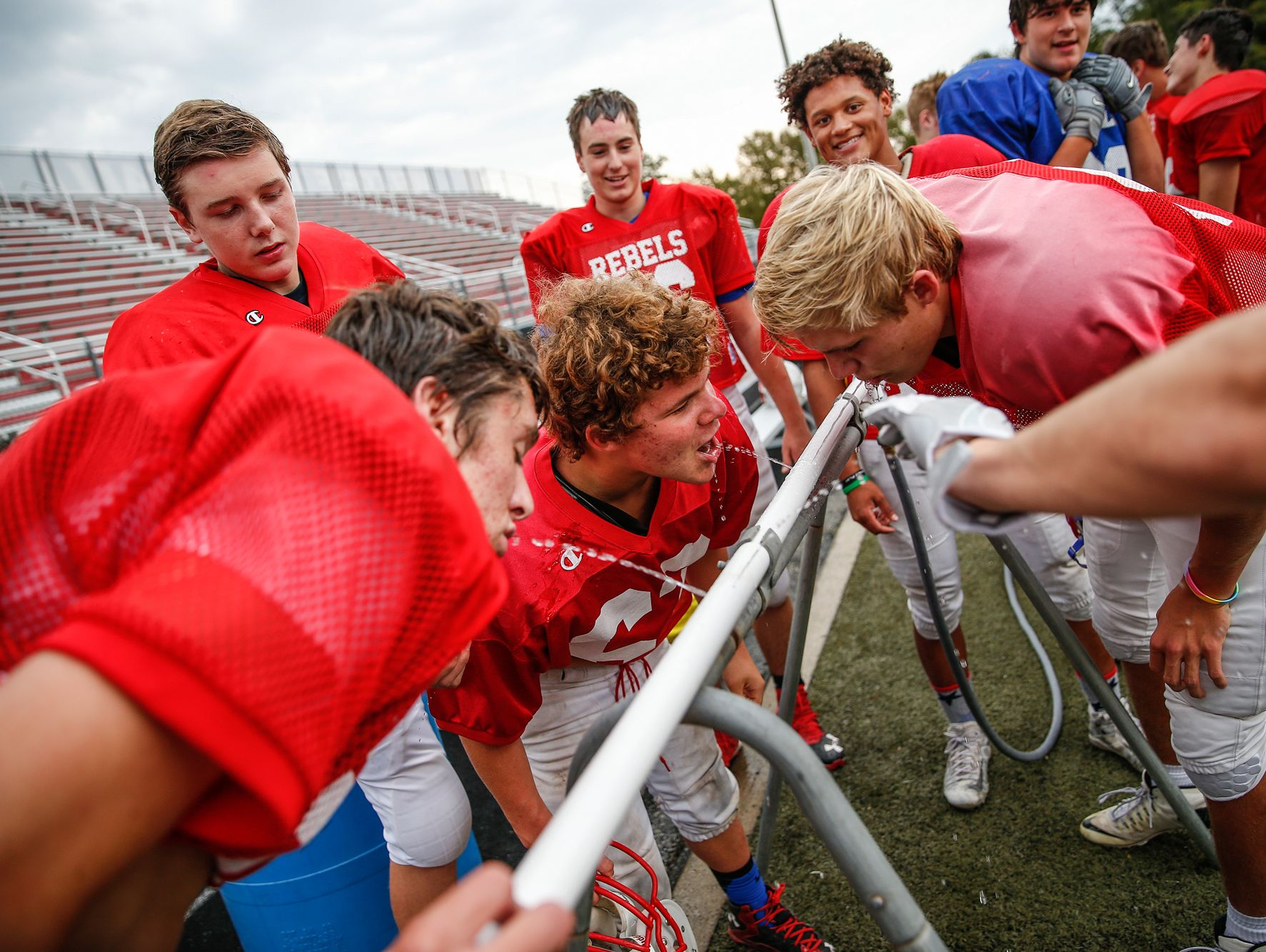 Roncalli Rebels nose tackle Max Quebe, middle, a 5-foot-2-inch, 135-pound Russian adoptee, gets a drink alongside other teammates after a drill during practice on Oct. 19, 2016.