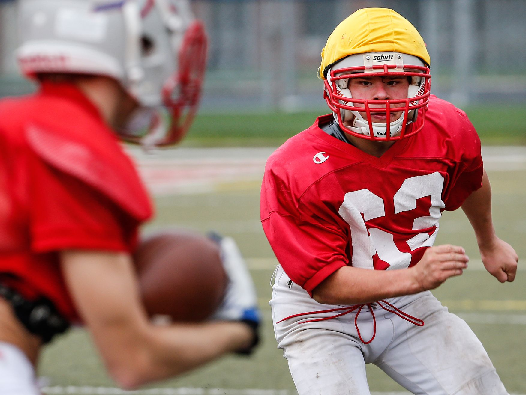 Roncalli Rebels nose tackle Max Quebe, a 5-foot-2-inch, 135-pound Russian adoptee, eyes a ball runner during practice on Oct. 19, 2016.