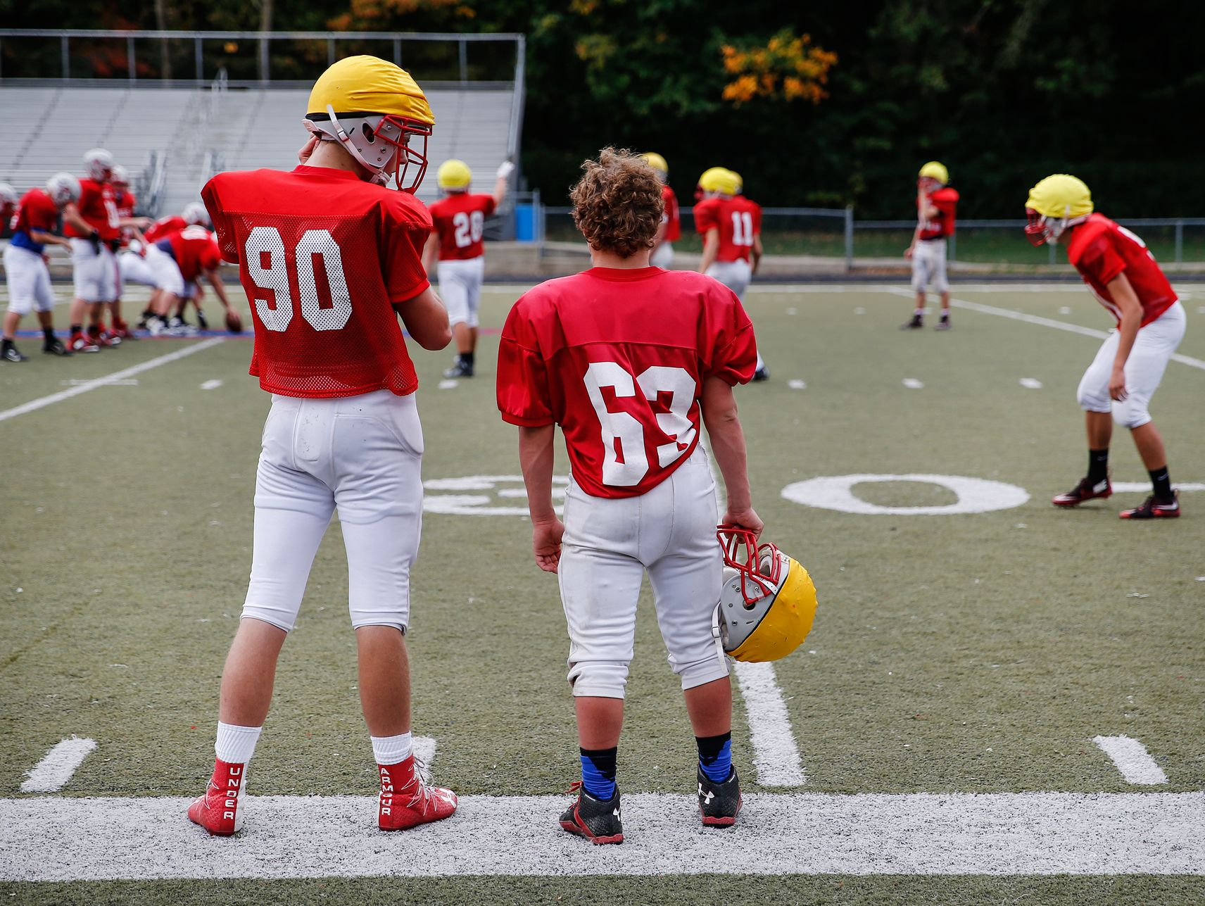 Roncalli Rebels nose tackle Max Quebe, a 5-foot-2-inch, 135-pound Russian adoptee, talks with sophomore Will King (90) on the sidelines during practice on Oct. 19, 2016.