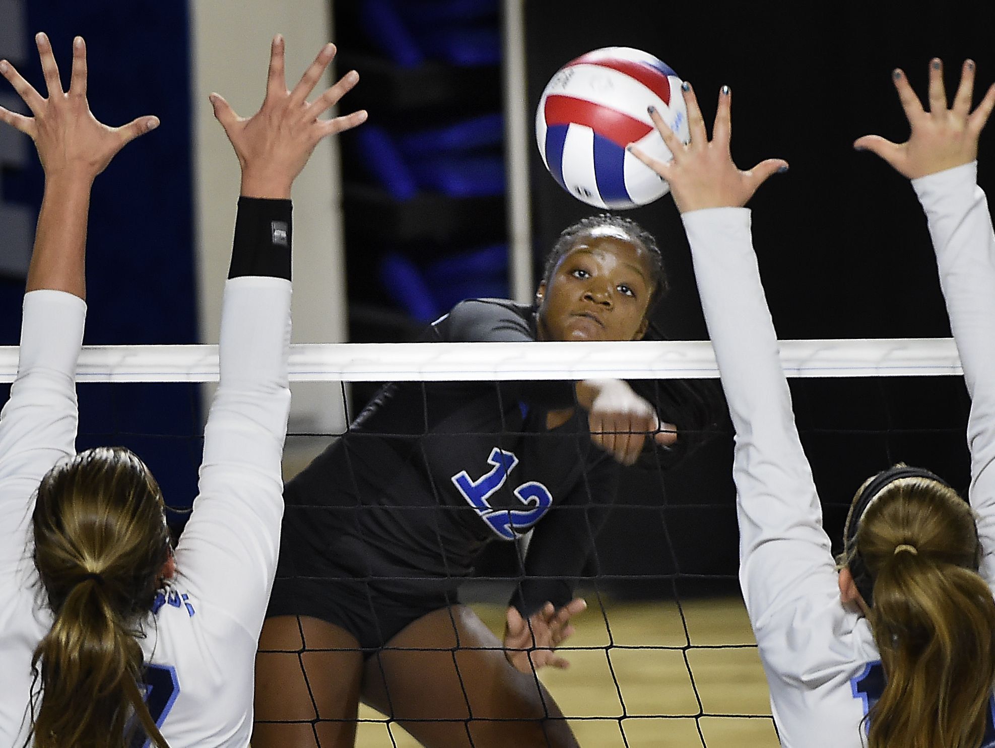Kamryn Carter (12) drills a shot between two defenders as Brentwood plays Hardin Valley at MTSU's Murphy Center during the TSSAA volleyball state tournament on Oct. 20, 2016.