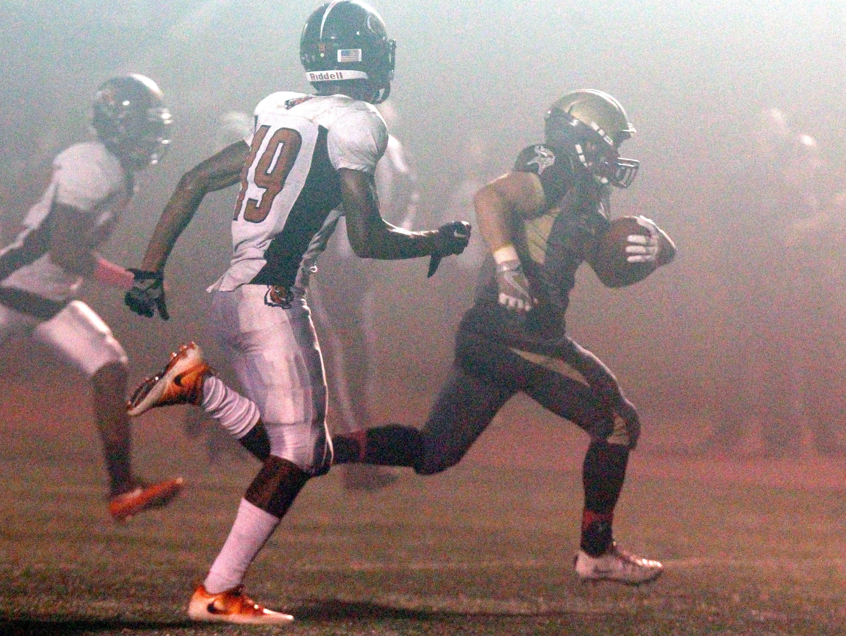 Clarkstown South's Ryan Thomas runs through the fog for a touchdown during a Class AA football quarterfinal with Spring Valley at Clarkstown South Oct. 21, 2016.