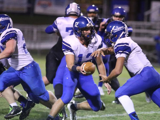 North Harrison's Avery Blocker hands off to Jaylen Peake in the Cougars' 17-14 win over Charlestown.