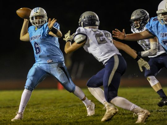 Freehold Township quarterback Charles Sabbagh throws a pass under pressure. (Photo: Jeff Granit)
