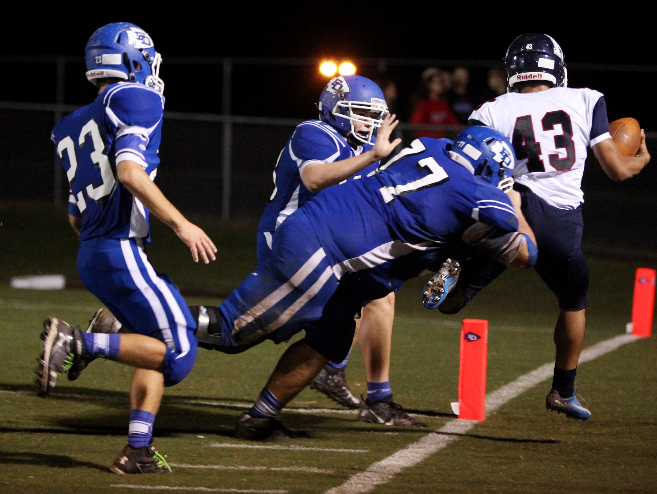 Fort Defiance's Dakota Morris, center, and Dillon Stickley push Harrisonburg's Roberto Gonzalez-Cavazos out-of-bounds as he tries for a two-point conversion during the second quarter of the game on Friday, Oct. 21, 2016 at Fort Defiance.