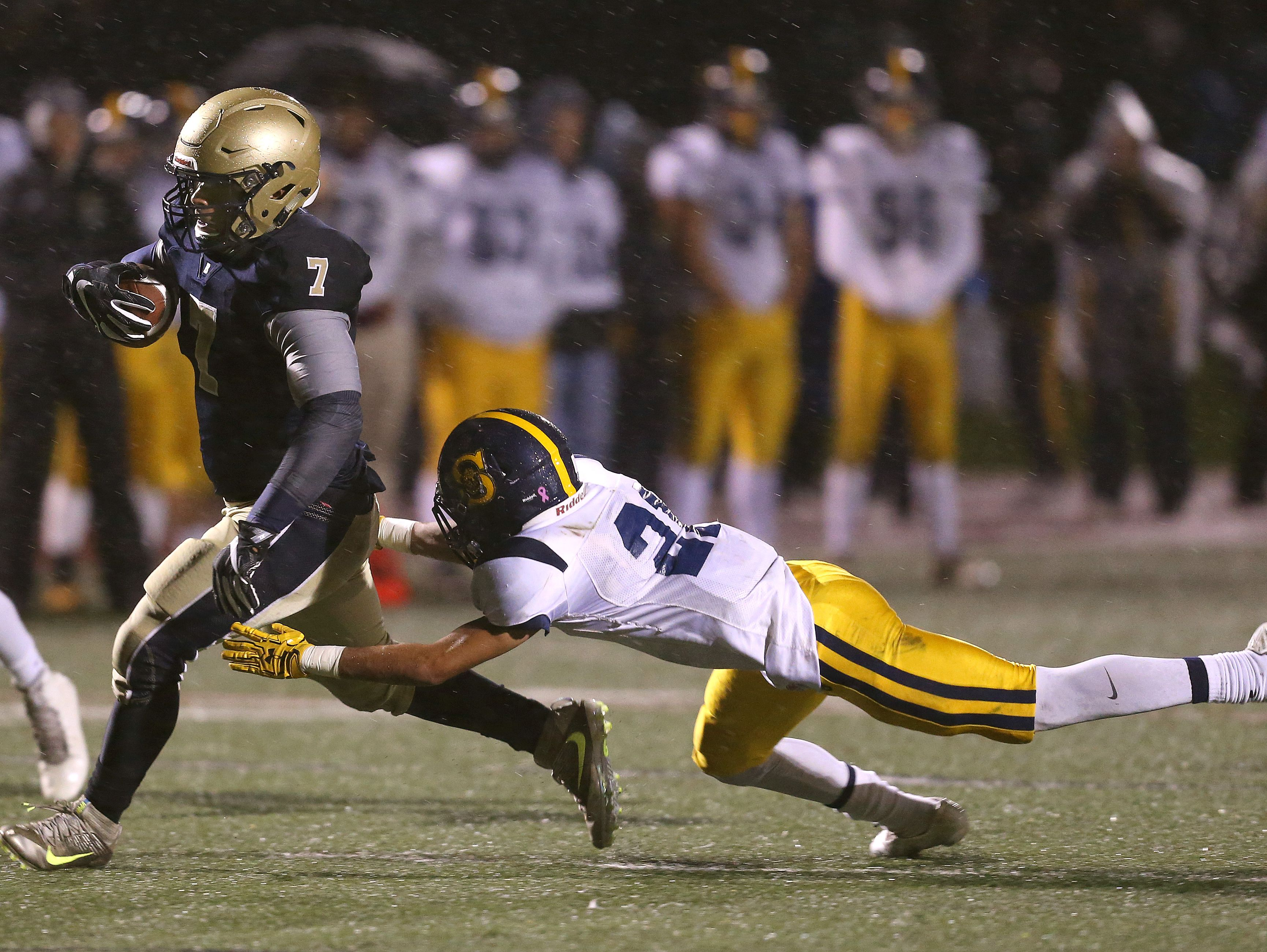 Brighton running back Jason Cunningham slips a tackle by Spencerport's Savion Stinson and scores a touchdown.