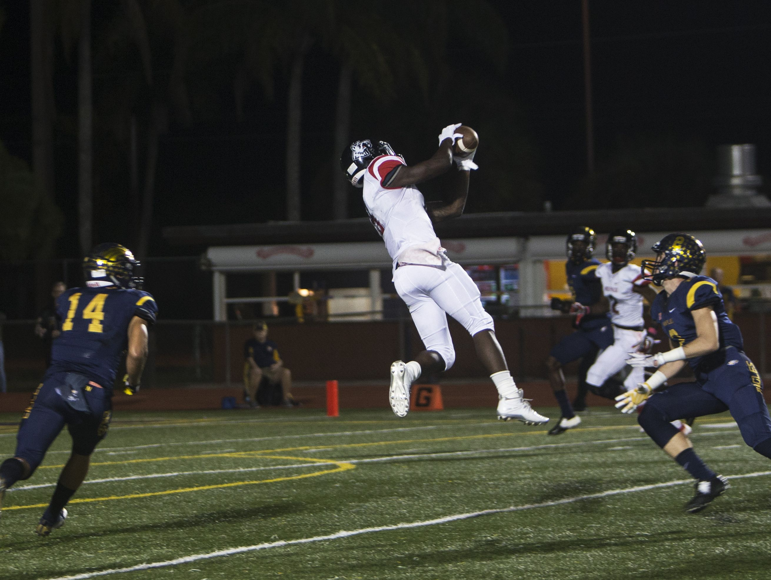 South Fort Myers running back E'Quan Dorris jumps to catch the ball during their matchup against Naples at Staver Field on Friday,