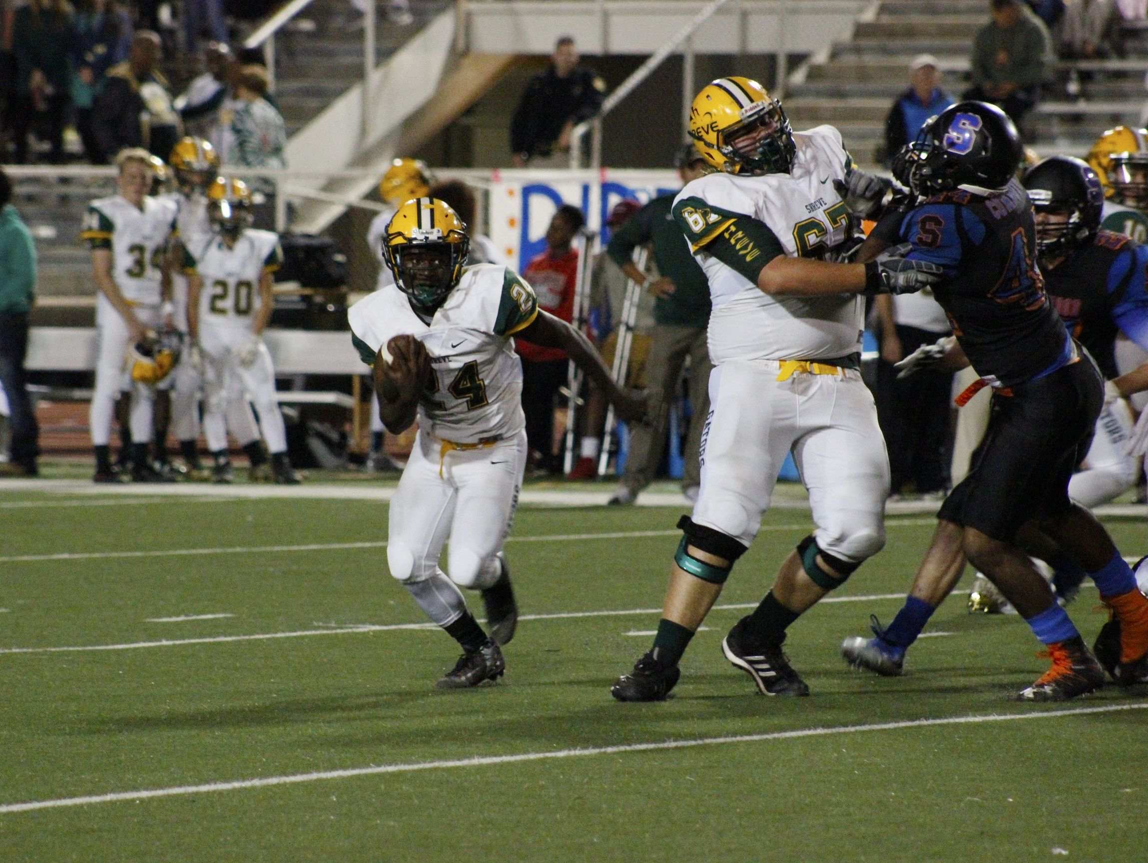 Demarcus McCall (24) for the Captain Shreve Gators rushes around the Southwood Cowboys defense on Friday night at Lee Hedges Stadium in Shreveport.