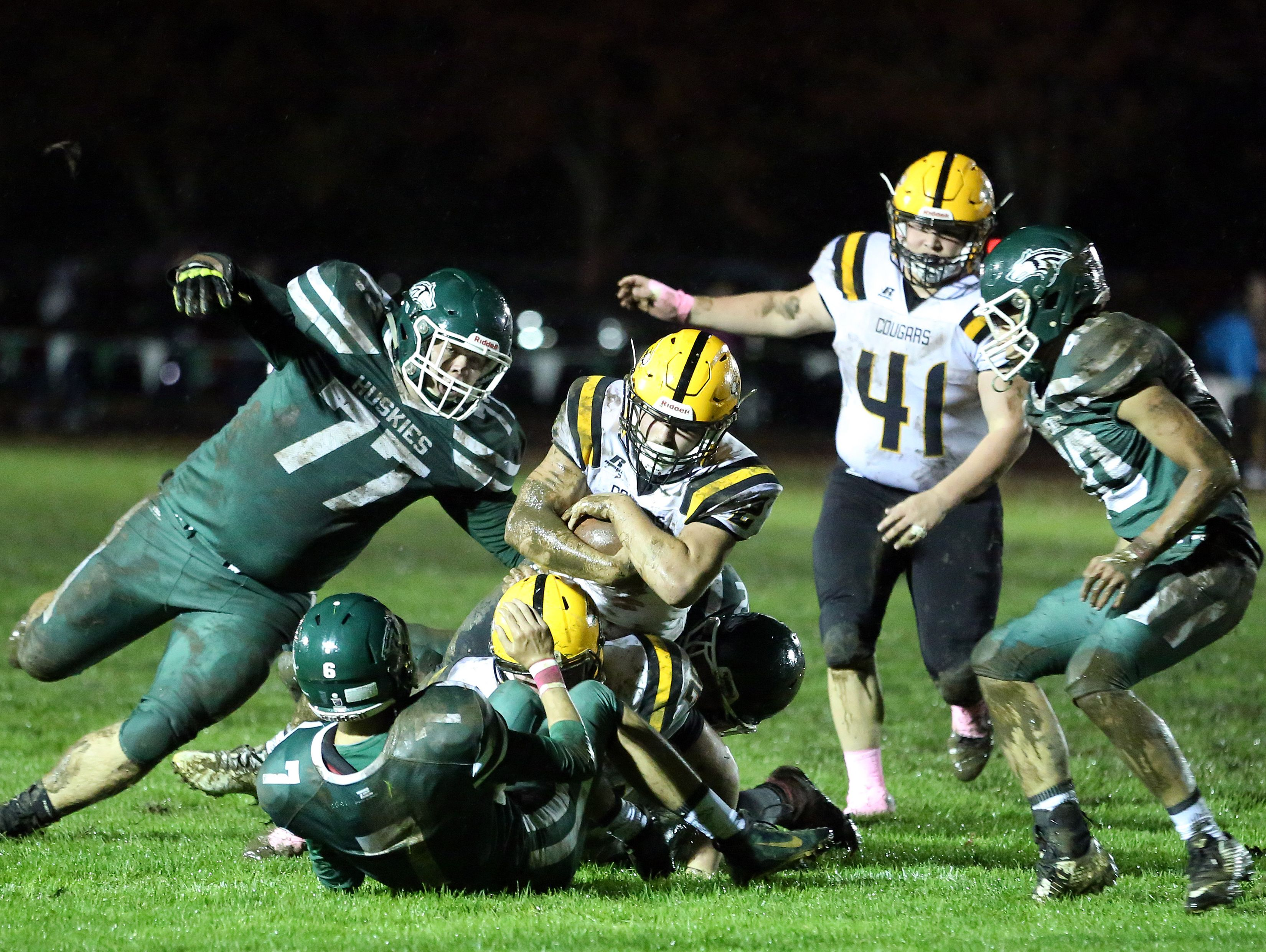 North Marion defenders take down Cascade's Justin Marcott in an Oregon West Conference game on Friday, Oct. 21, 2016.