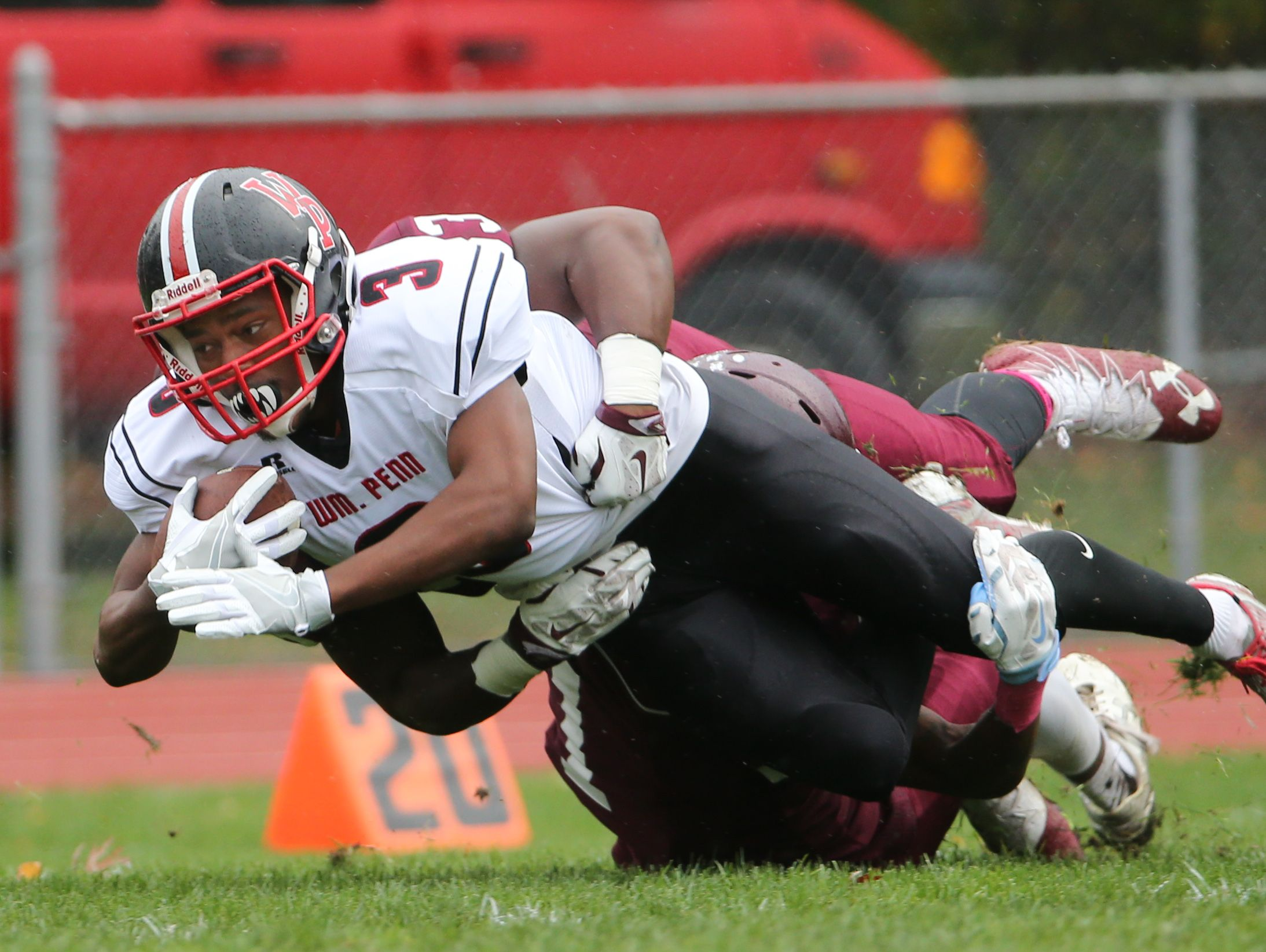 William Penn's Joe Greenwood dives for extra yardage while being tackled by Concord's Byron Simpson in the first quarter of the Colonial's 14-7 win over Concord.