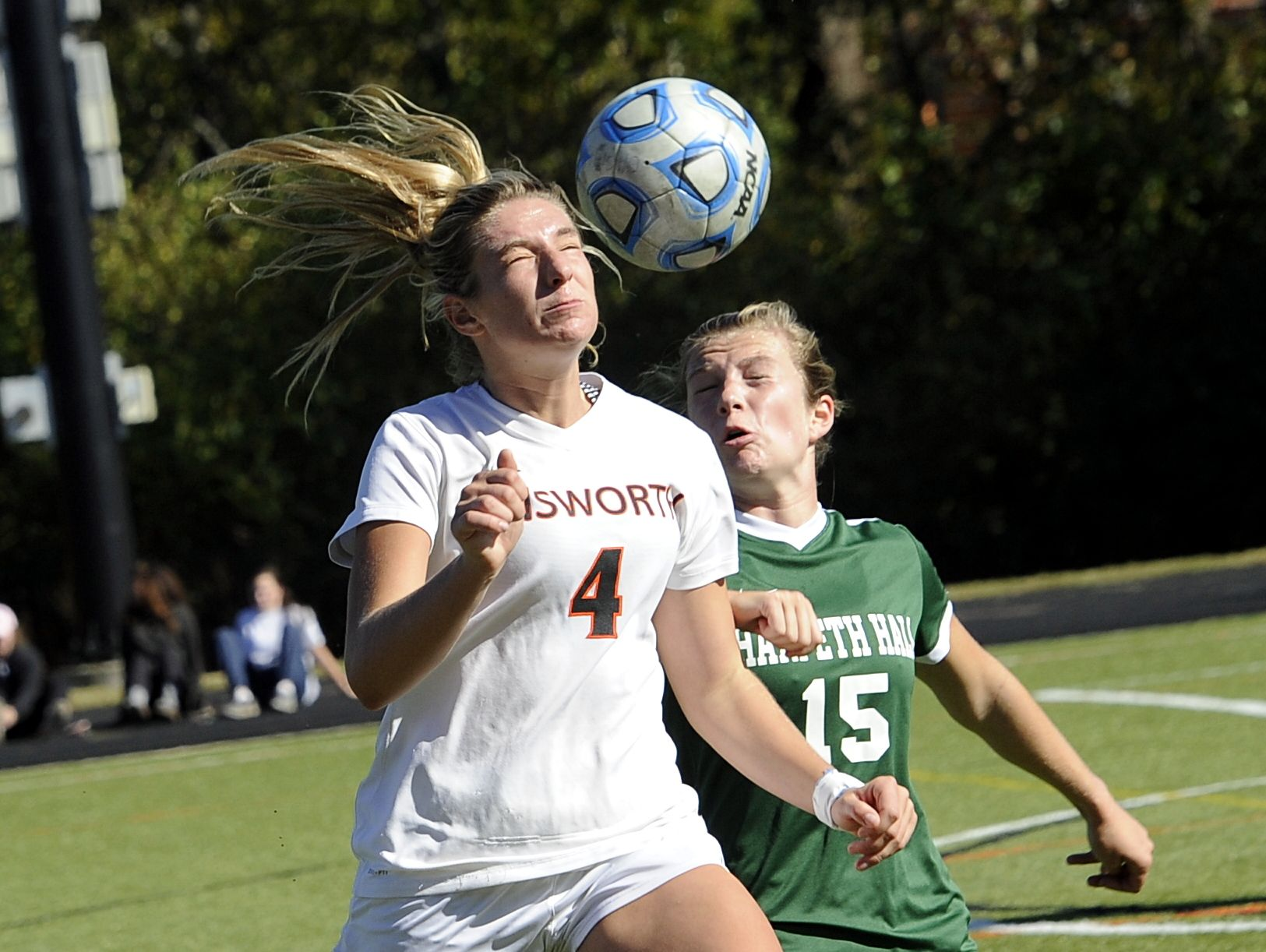 Ensworth senior Gracie Munson heads a bouncing ball in front of Harpeth Hall senior Lauren Stringfield on Oct. 22, 2016.