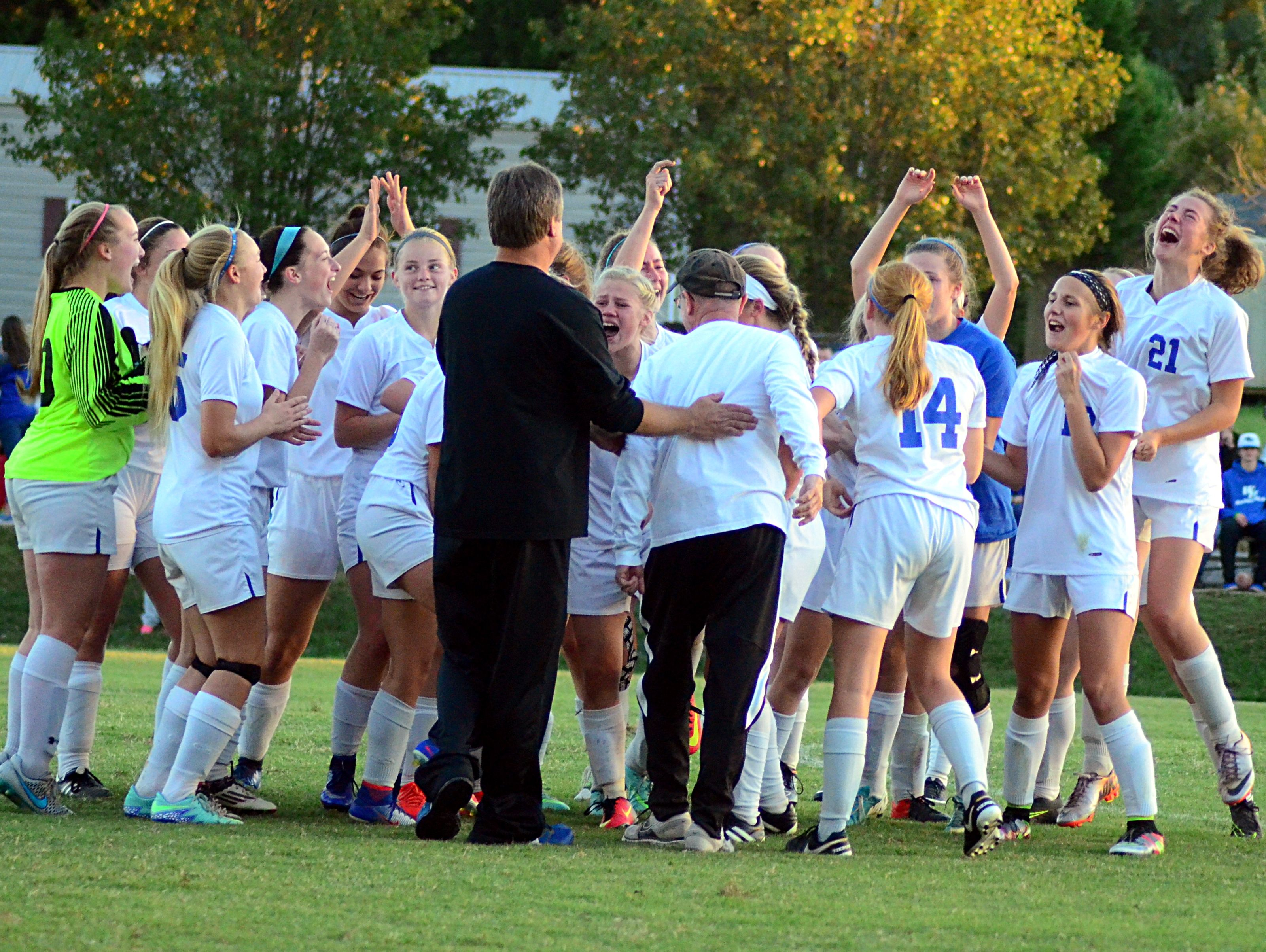 White House High players and coaches celebrate after the Lady Devils' 3-1 victory over Page in Saturday's Class A-AA sectional match.
