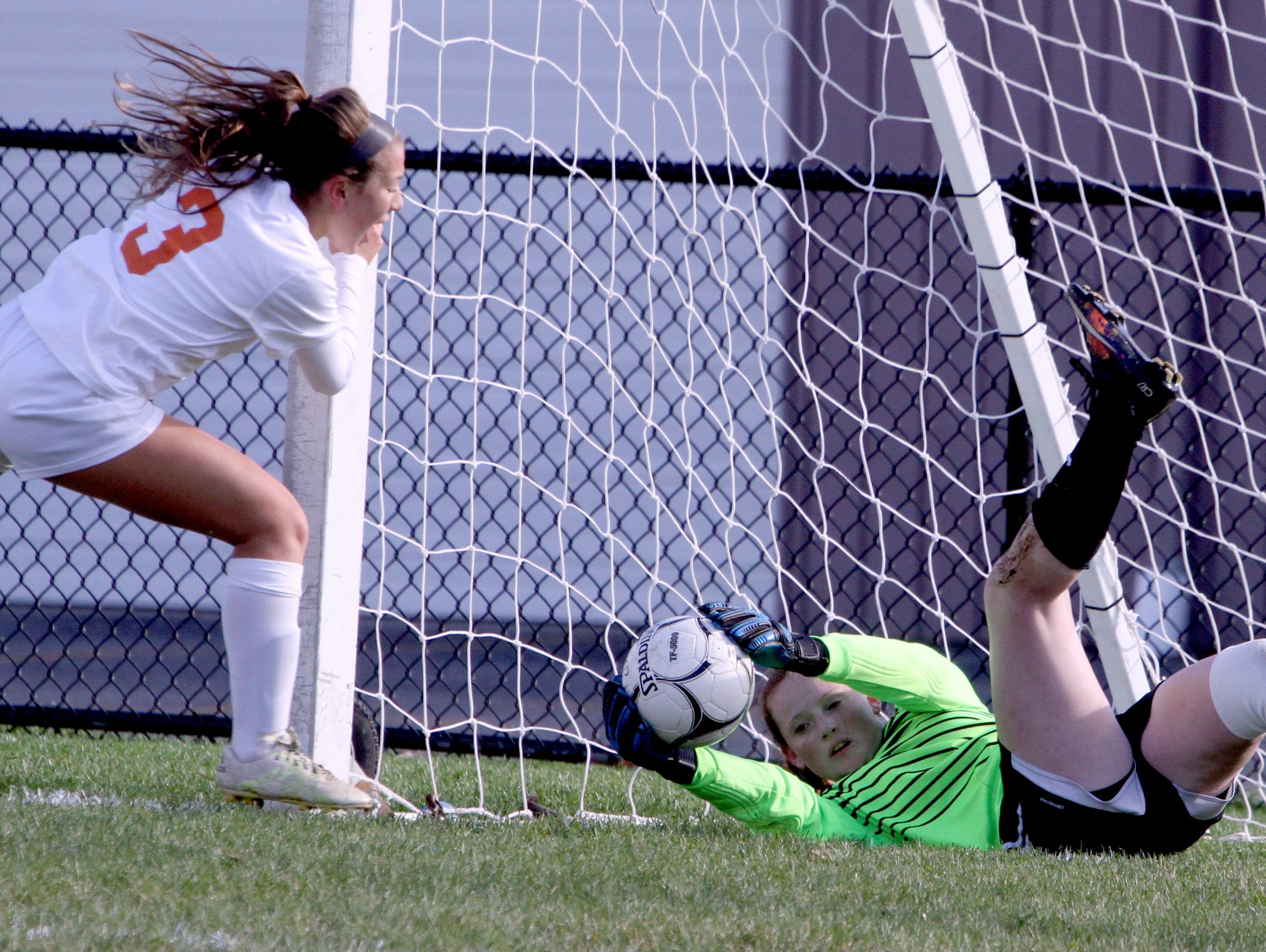 With Horace Greeley's Emma Ardizzone closing in, Mahopac goalie Julia Mende holds on the ball during the Class AA girls soccer semifinal game at Horace Greeley in Chappaqua Oct. 25, 2016. Mahomac defeated Greeley on penalty kicks.