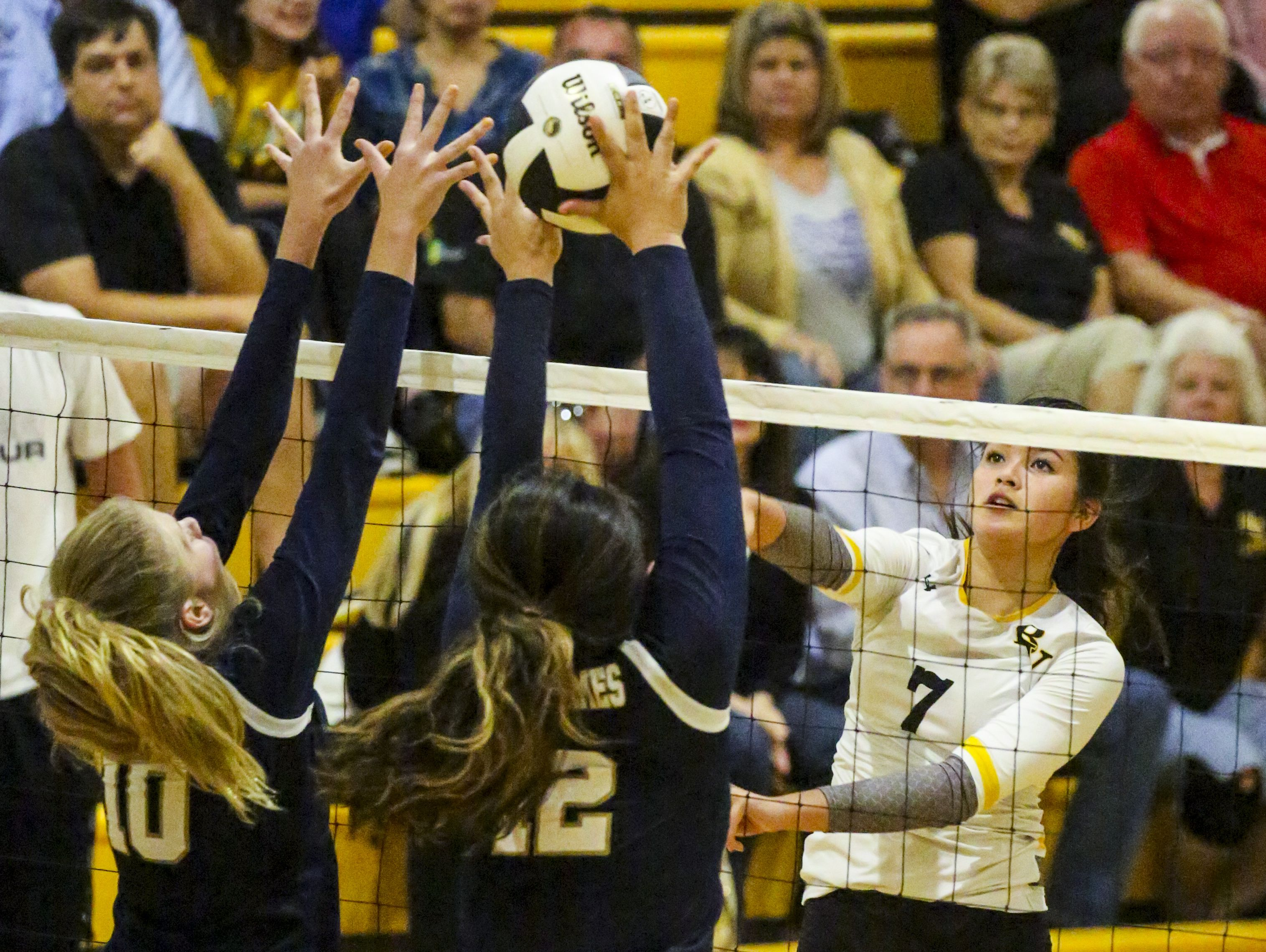 Bishop Verot's Teya Leonard hits through Holy Name defenders Megan Przedpelski and Rachel Rosales as Tampa Academy of Holy Names played Bishop Verot in their Region 5A-3 volleyball quarterfinal.