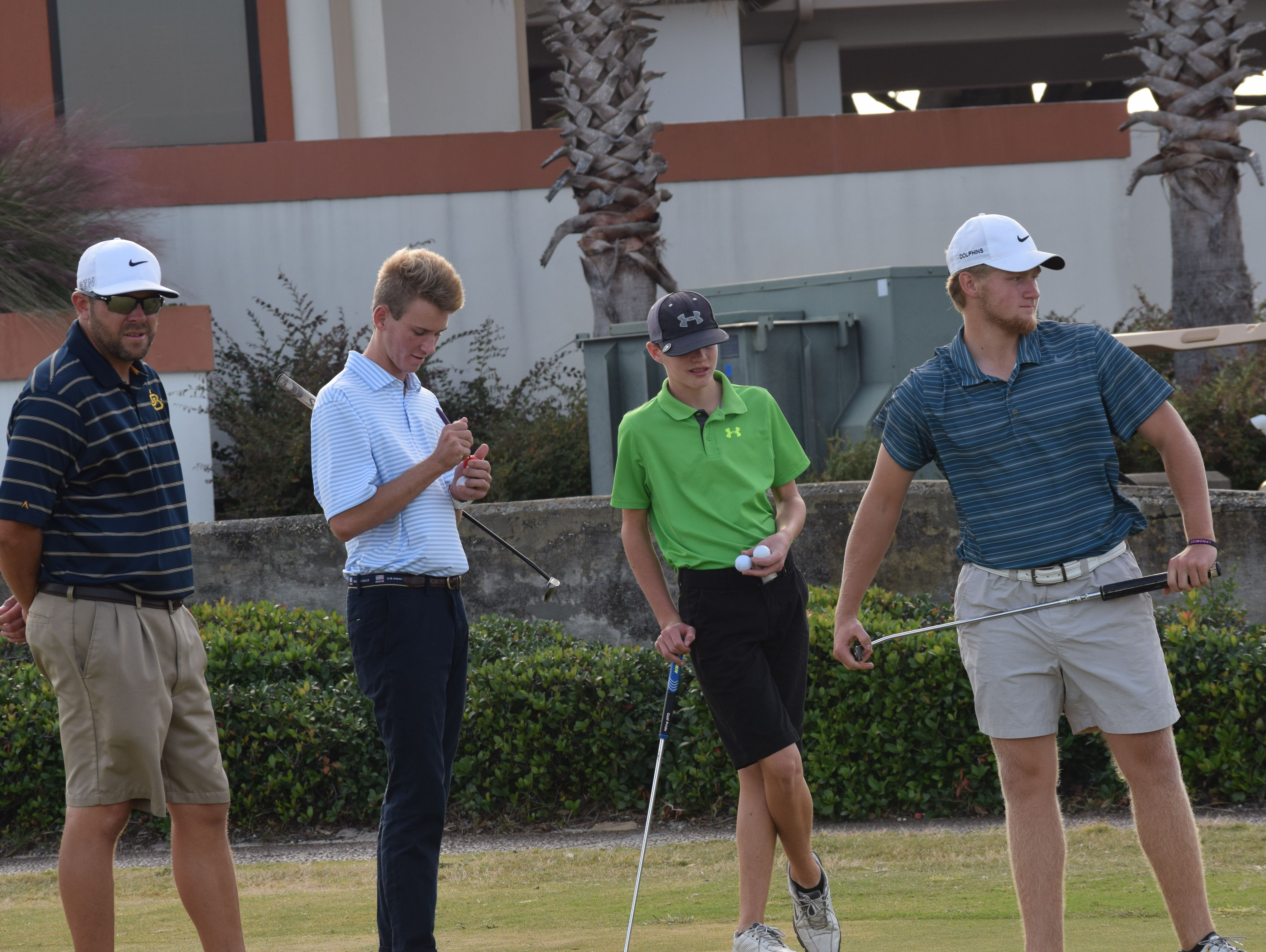 Gulf Breeze High boys golf coach Adam Smith watches three of his players, Brian Richards (left), Luke Ellis (middle) and RJ Phillips on putting green Wednesday at Tiger Point Golf Club in preparation for next week's Class 2A state tournament near Orlando.