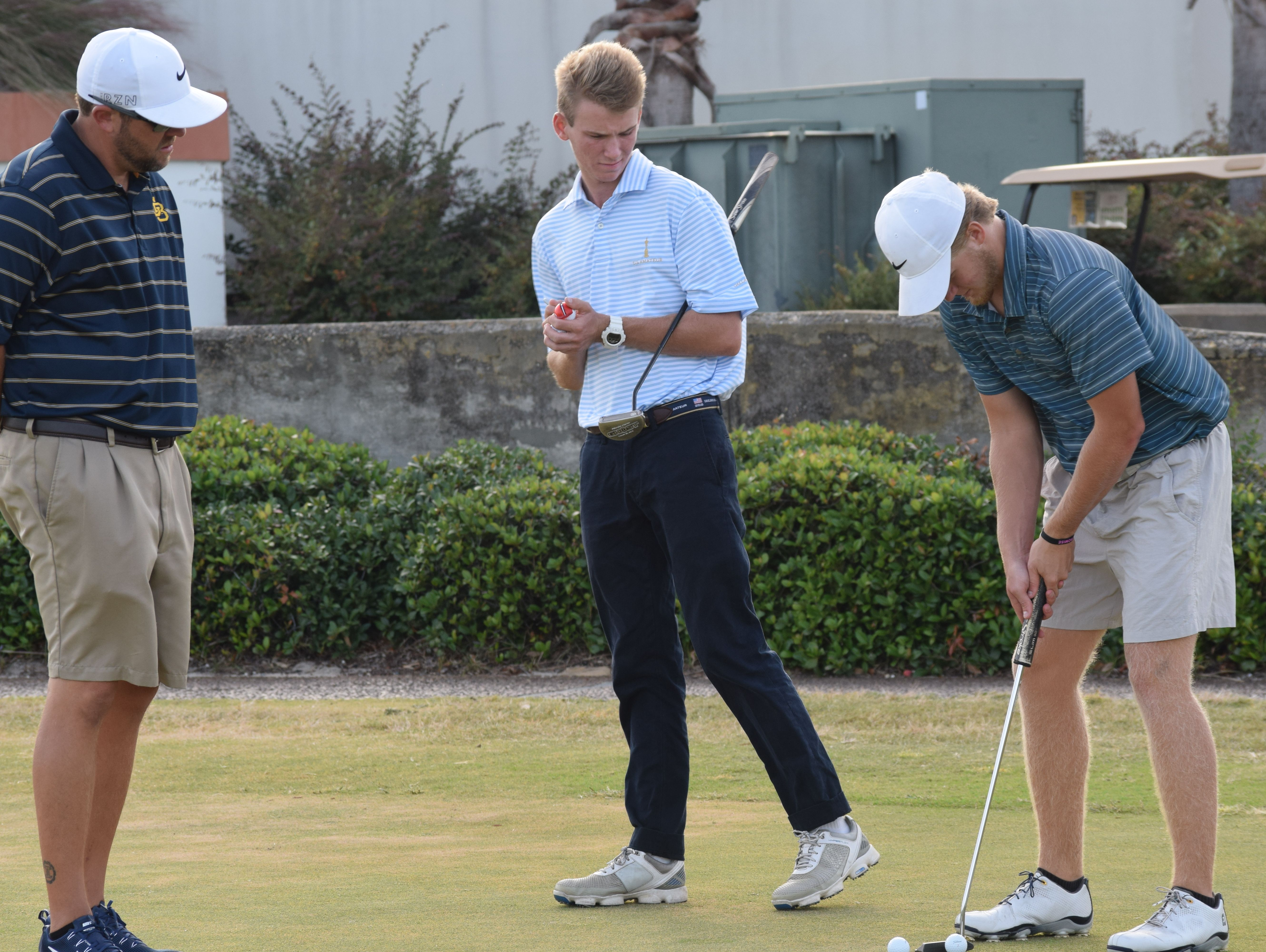 Gulf Breeze coach Adam Smith watches seniors Brian Richards and RJ Phillips practice Wednesday at Tiger Point. The Dolphins are one of four area teams in boys and girls classifications participating in the state prep golf tournament.