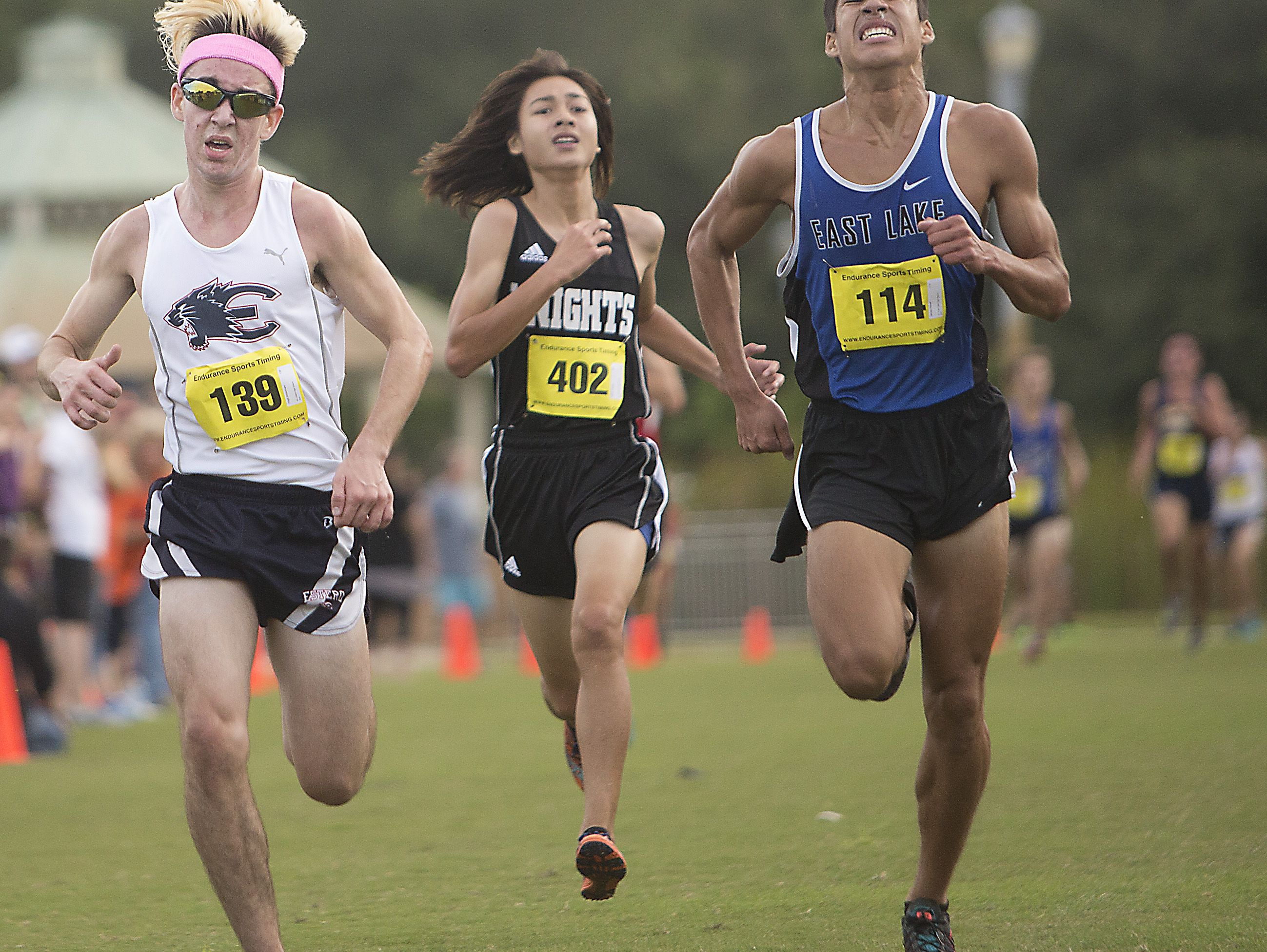 From left, Hugh Brittenham, Estero High School, Ethan Geiger, Robinson High School, and James Hasell, East Lake High School sprint to the finish line during the FHSAA 3A Region district championships at Estero Community Park.