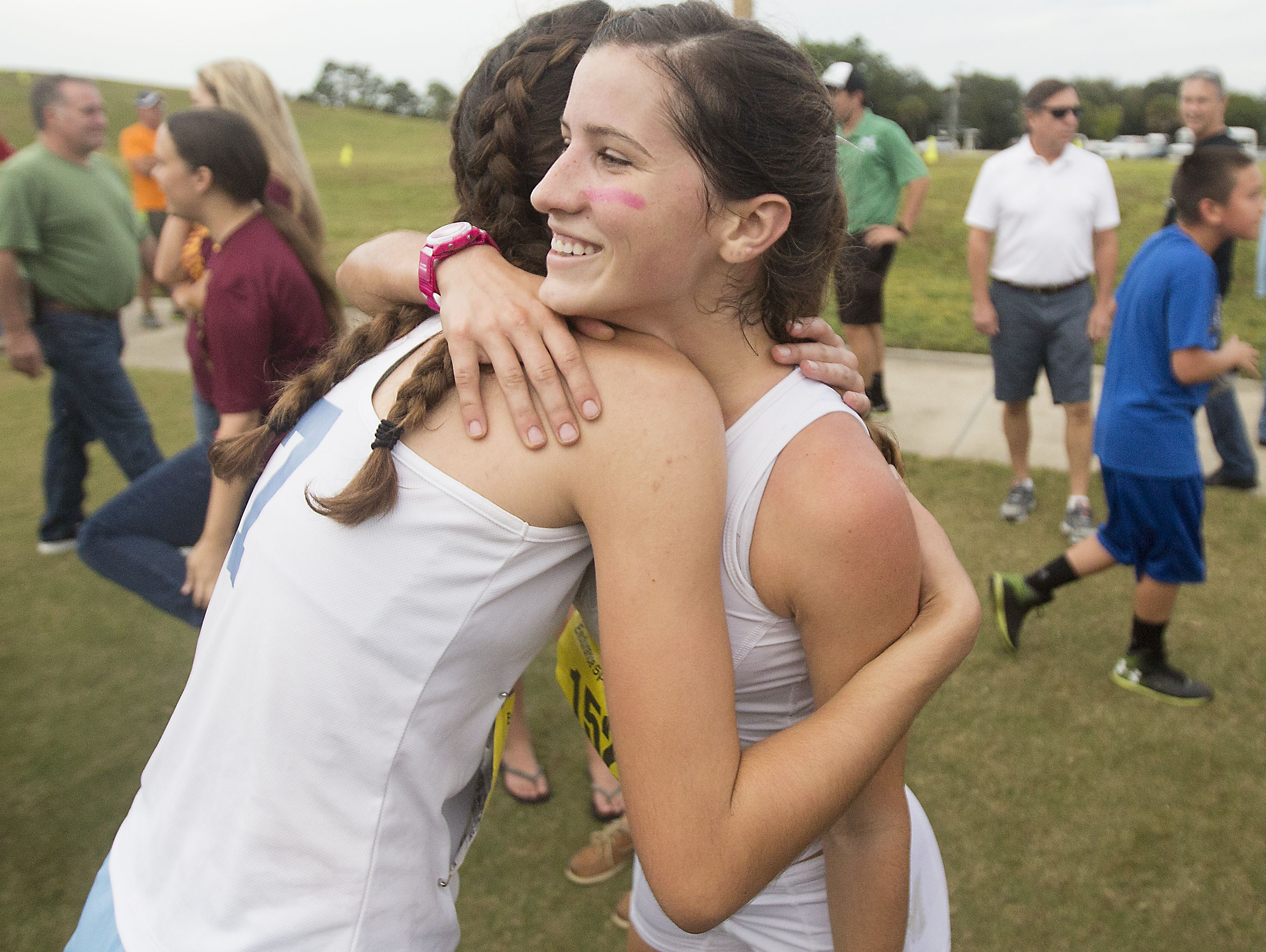 Fort Myers High School x-country runner Krissy Gear gets a hug from a competitor after winning the FHSAA 3A District finals at Estero Community Park on Friday. The Fort Myers High School girls also won the over all title.
