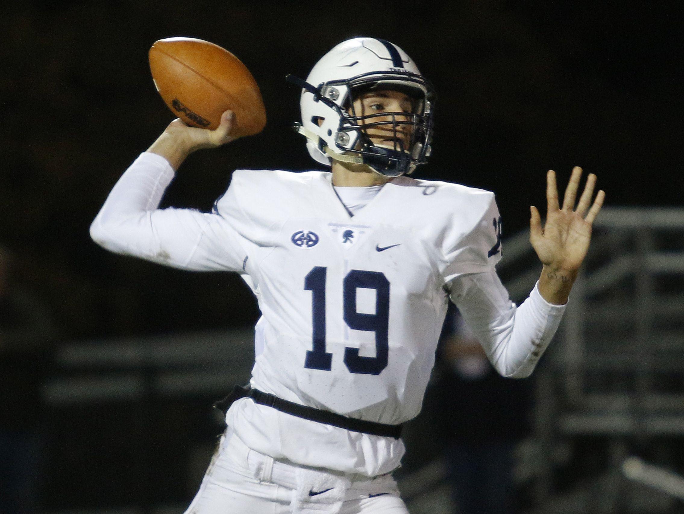 East Lansing quarterback Hunter Helmic throws a pass for a touchdown against DeWitt Friday, Oct. 28, 2016, in DeWitt, Mich.