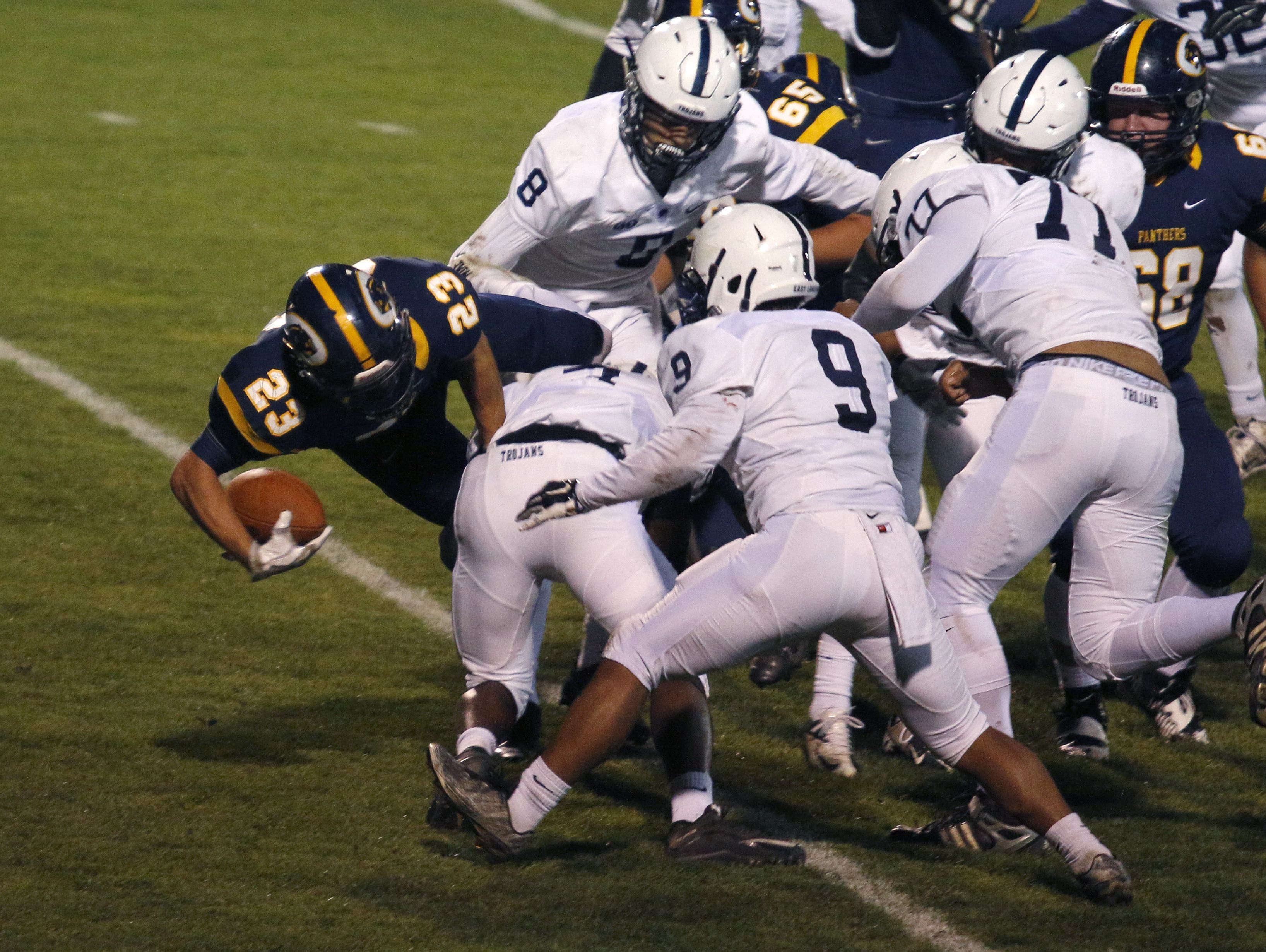 DeWitt's JD Ross (23) dives in for a touchdown against East Lansing's Roy Bellamy-Crawford (9), Blake Underwood (8), Mykel Thornton (77) and Darian Holbrook, left, Friday, Oct. 28, 2016, in DeWitt, Mich.