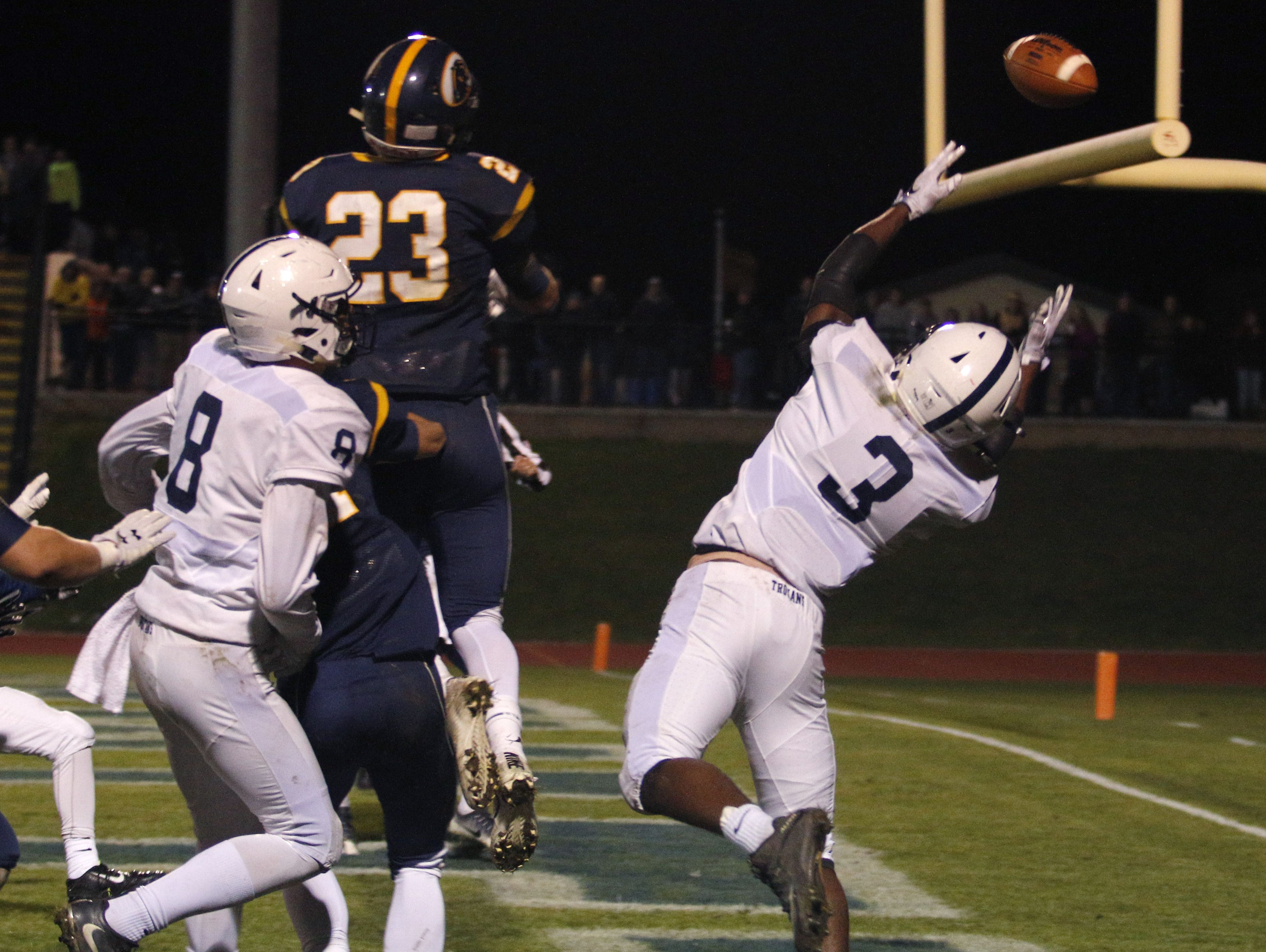 DeWitt's JD Ross (23) bats away a pass in the end zone at the close the first half against East Lansing's Darian Holbrook (3) and Blake Underwood (8) Friday, Oct. 28, 2016, in DeWitt, Mich.