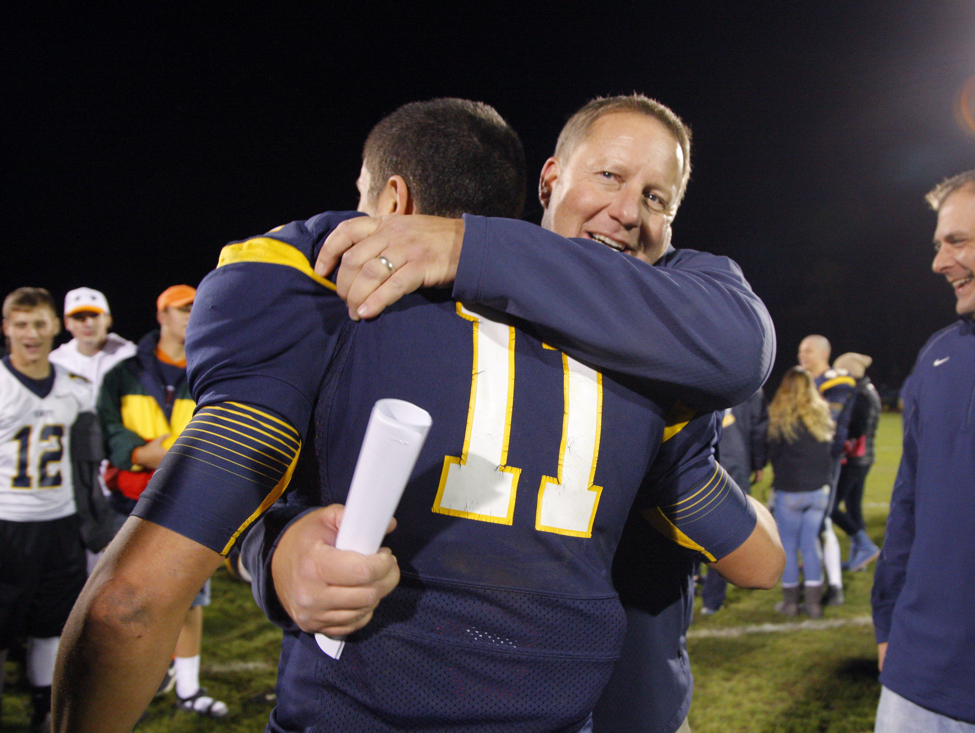 DeWitt coach Rob Zimmerman and Nicholas Simon celebrate following their 21-7 win over East Lansing Friday, Oct. 28, 2016, in DeWitt, Mich.