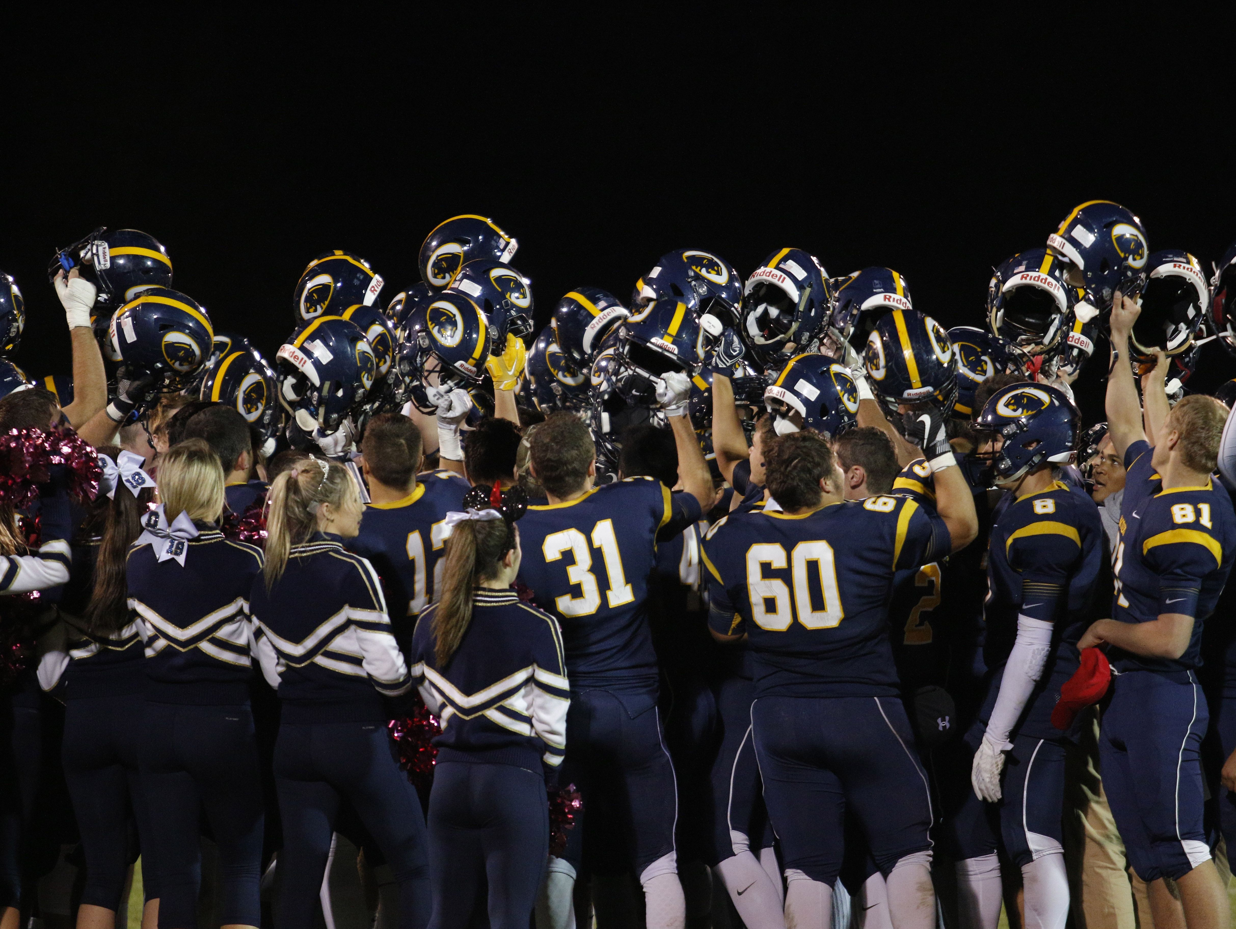 DeWitt players celebrate their 21-7 win over East Lansing Friday, Oct. 28, 2016, in DeWitt, Mich.