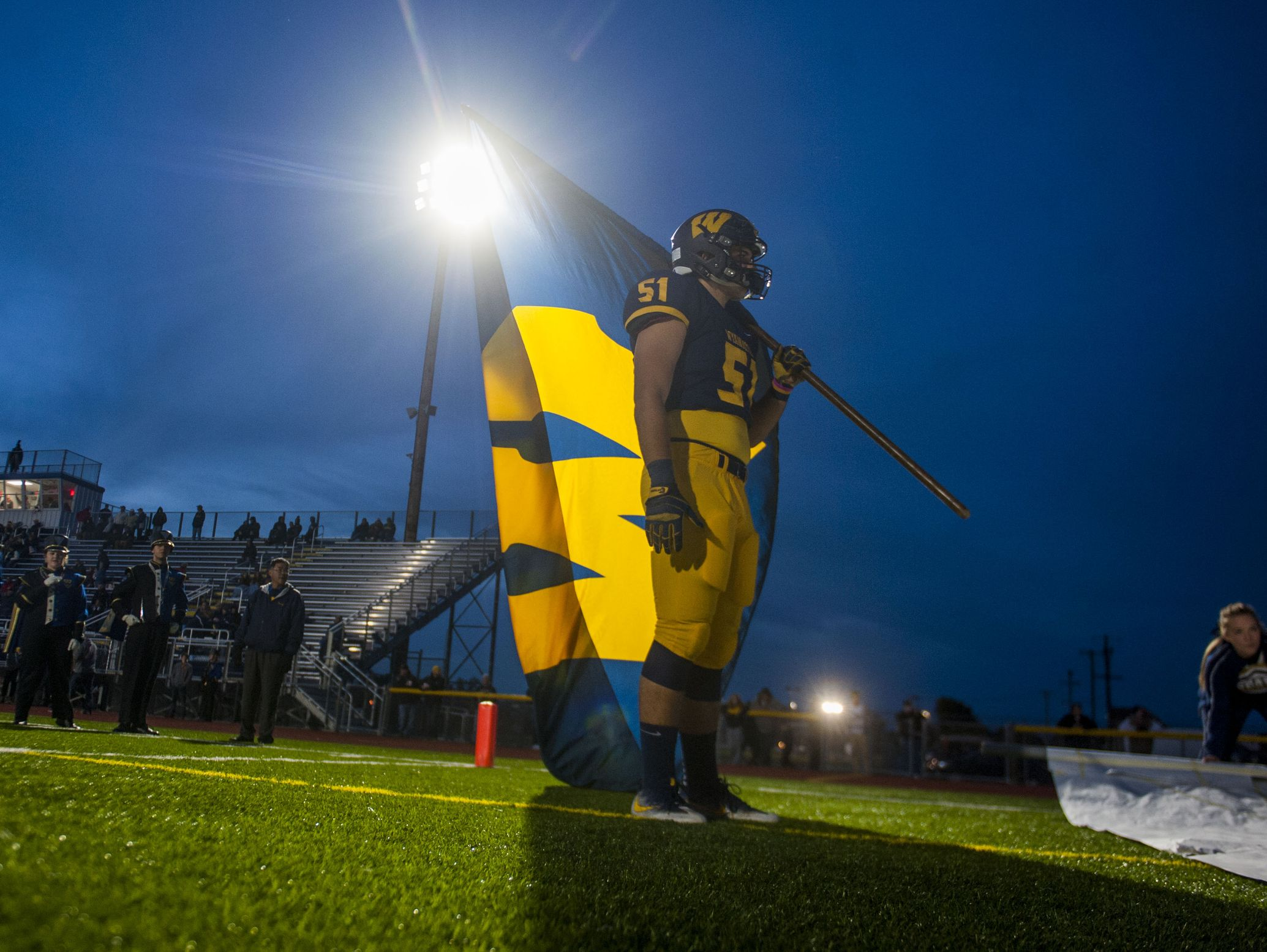 Wyandotte Roosevelt's Joshua Thompson (51) holds a flag prior to his team running out onto the field before Temperance Bedford's 43-21 win in the state playoffs Friday.
