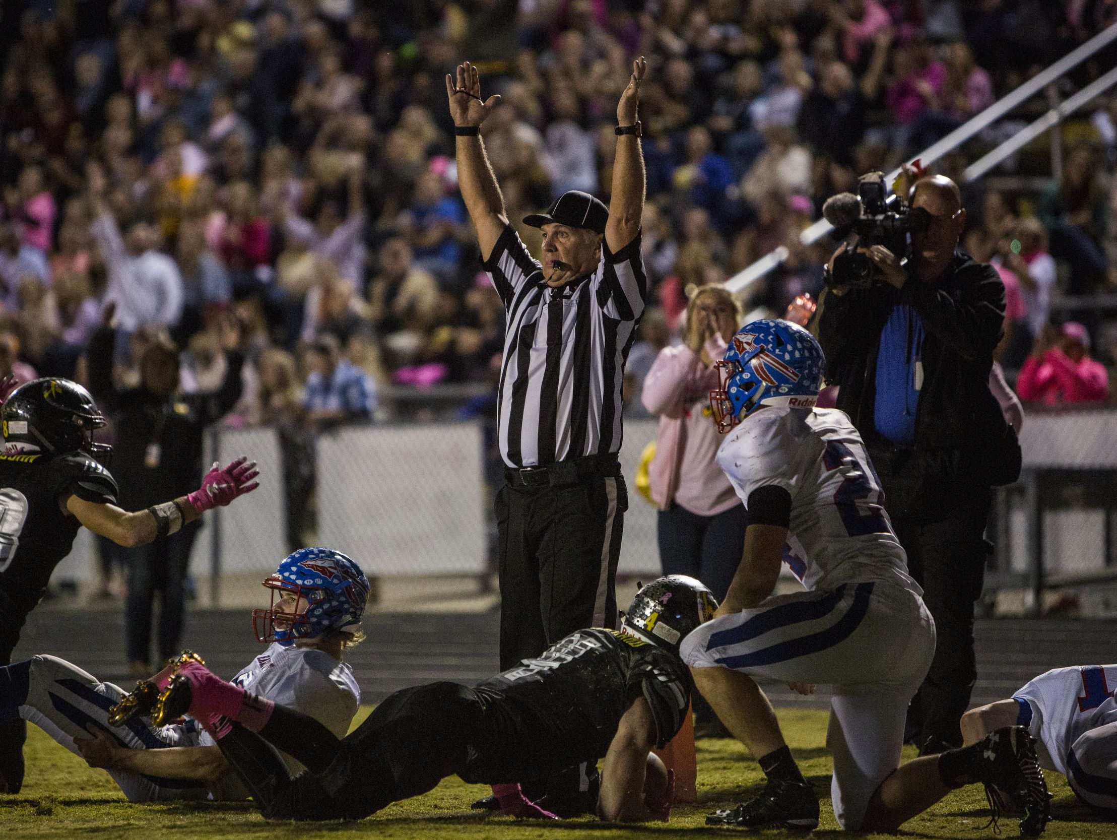 Referees single a touchdown late in the second quarter after Fairview High School's _ dives into the end zone.