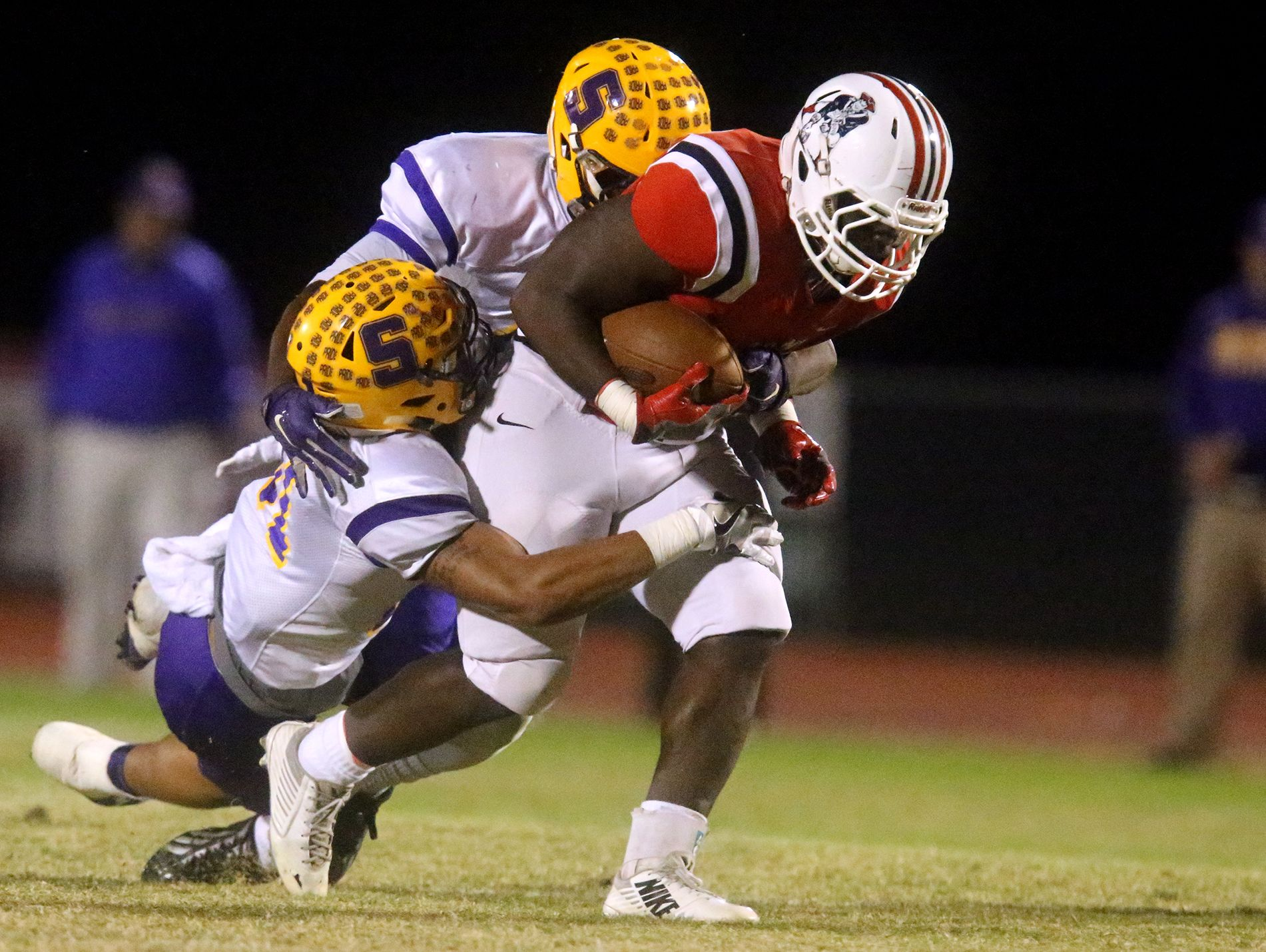 Oakland's Lontavious Wilson (27) runs the ball as Smyrna's Deven Sims (31) and Eric Recasner (41) try to bring Wilson down, on Friday, Oct. 28, 2016, at Oakland.