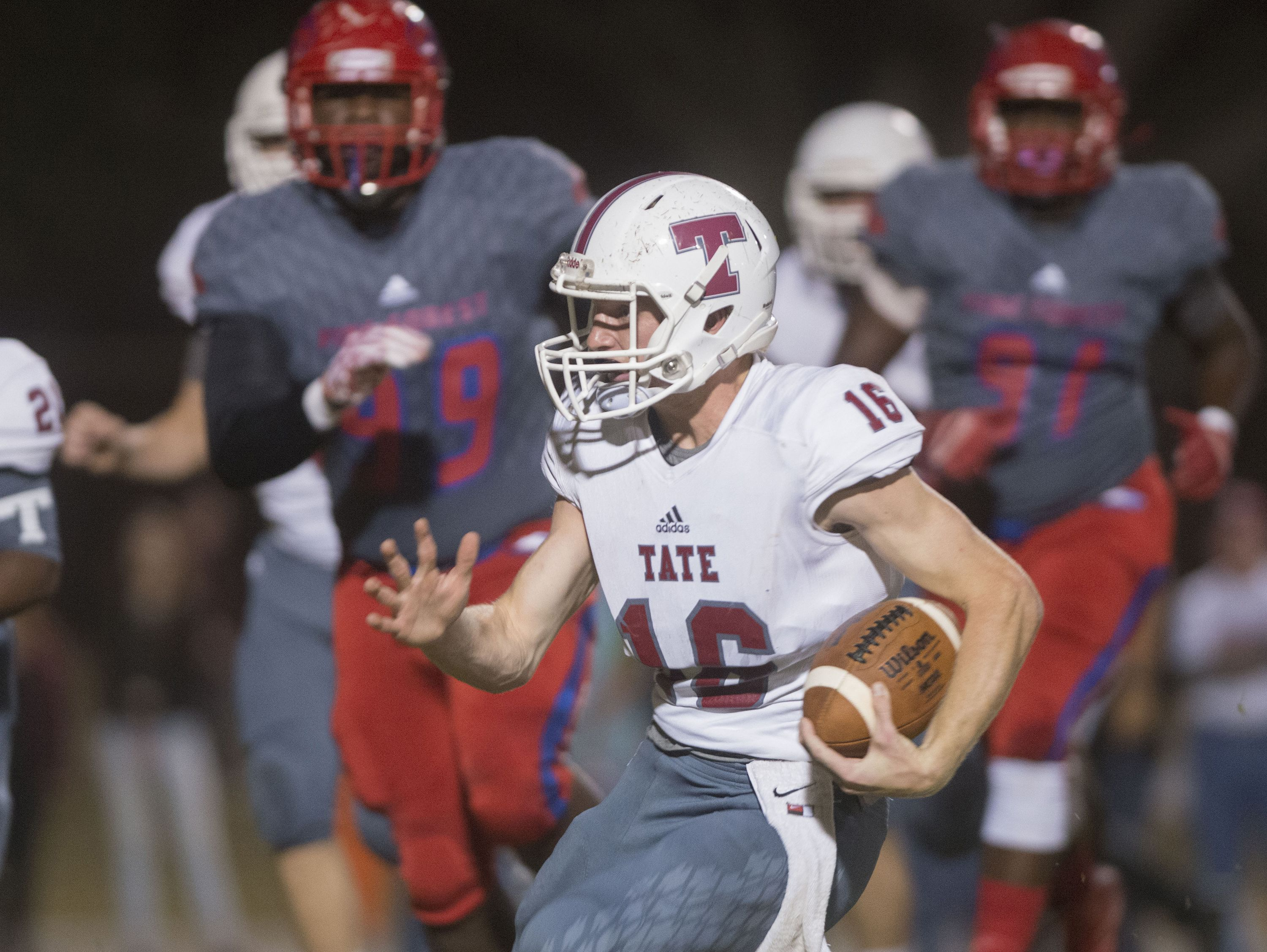 Tate High School quarterback, Jake Henry, (No.16) runs extra yards on a keeper during Friday night's district game.