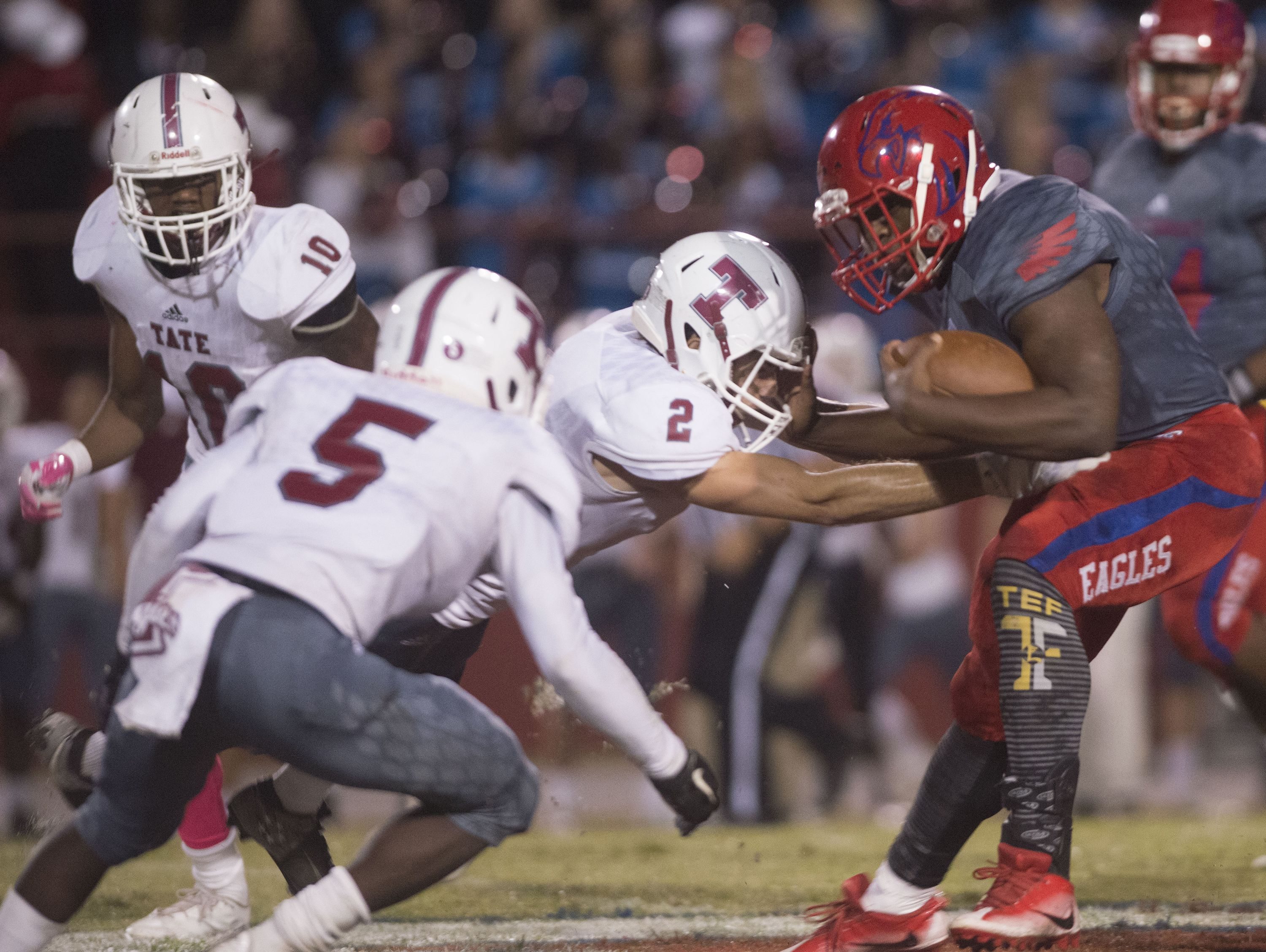 Tate High School's Alex Young, (No.2) and Bishod Clark, (No.5) stops Pine Forest High School's Xavier Saulsberry, (No. 15) behind the line for a loss during Friday night's district game.