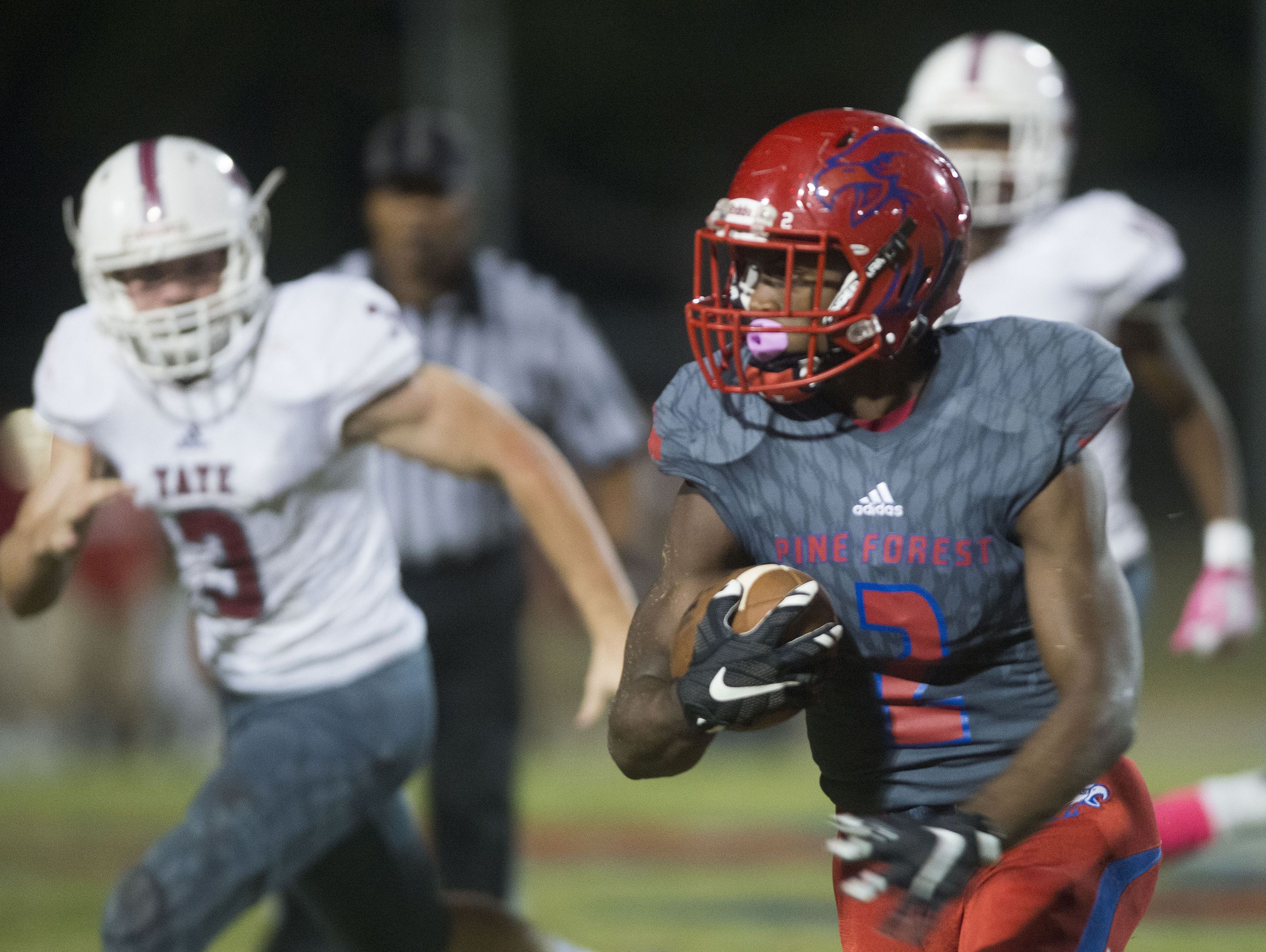 Pine Forest High School running back, Jaden Gardner, (No. 2) turns up field for a big gain against as the Tate High School defense gives chase during a winner take all district game Friday night.