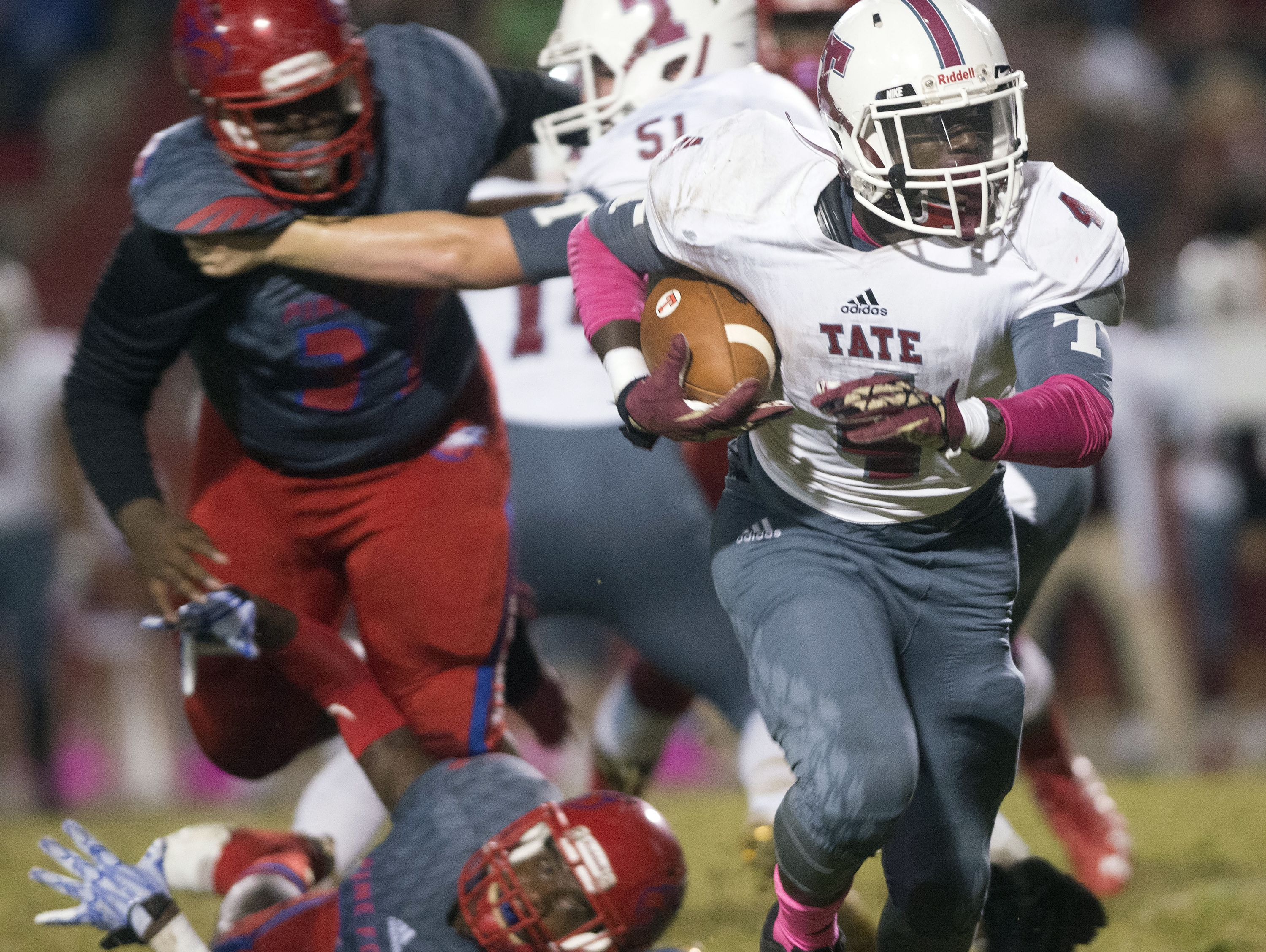 Tate running back, Ladarryl Paige, (No.4) breaks through the Pine Forest defensive line for extra yards during Friday night's winner take all district game.