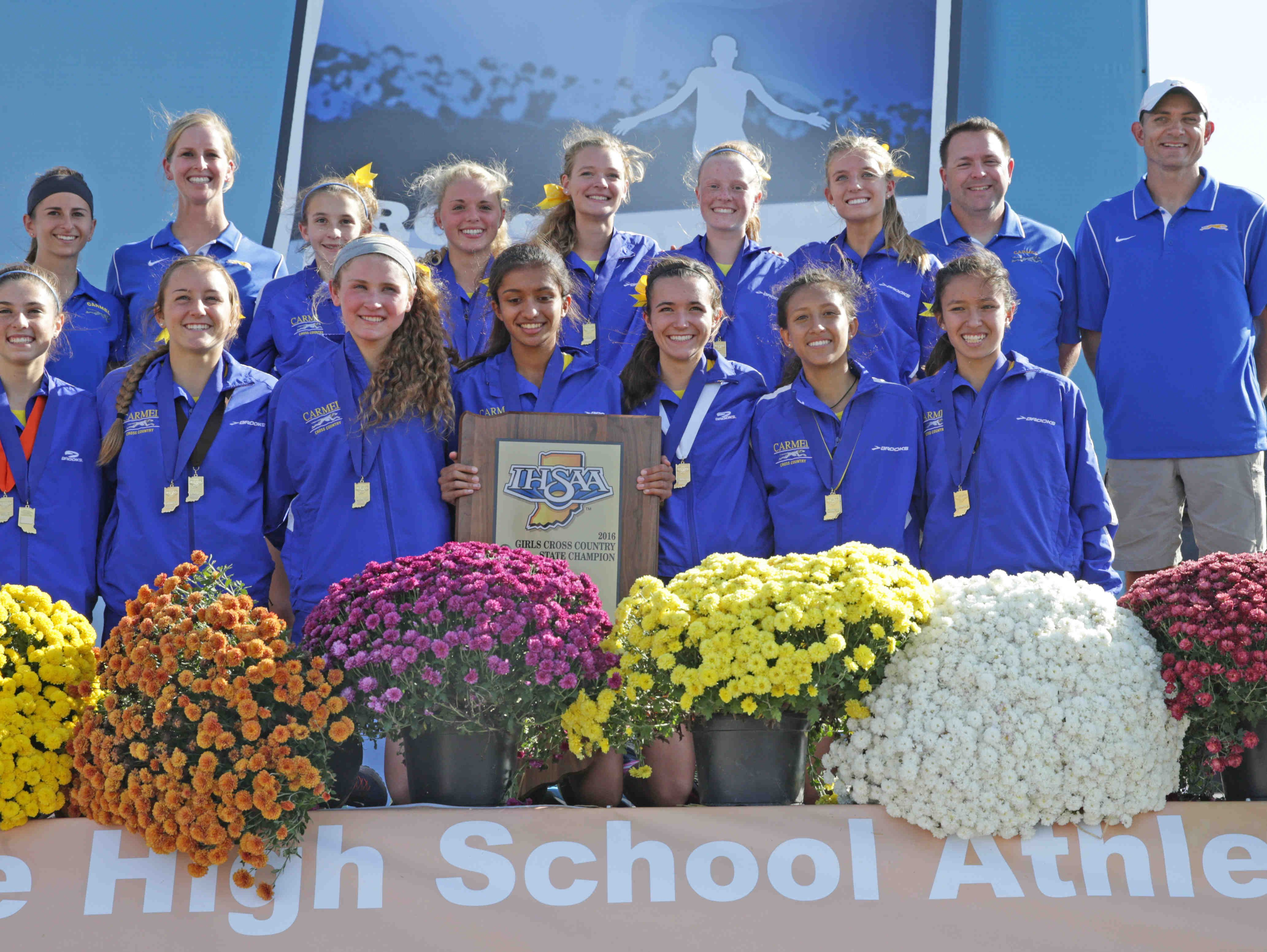 The Carmel girls cross-country team poses after claiming its seventh-straight state title.
