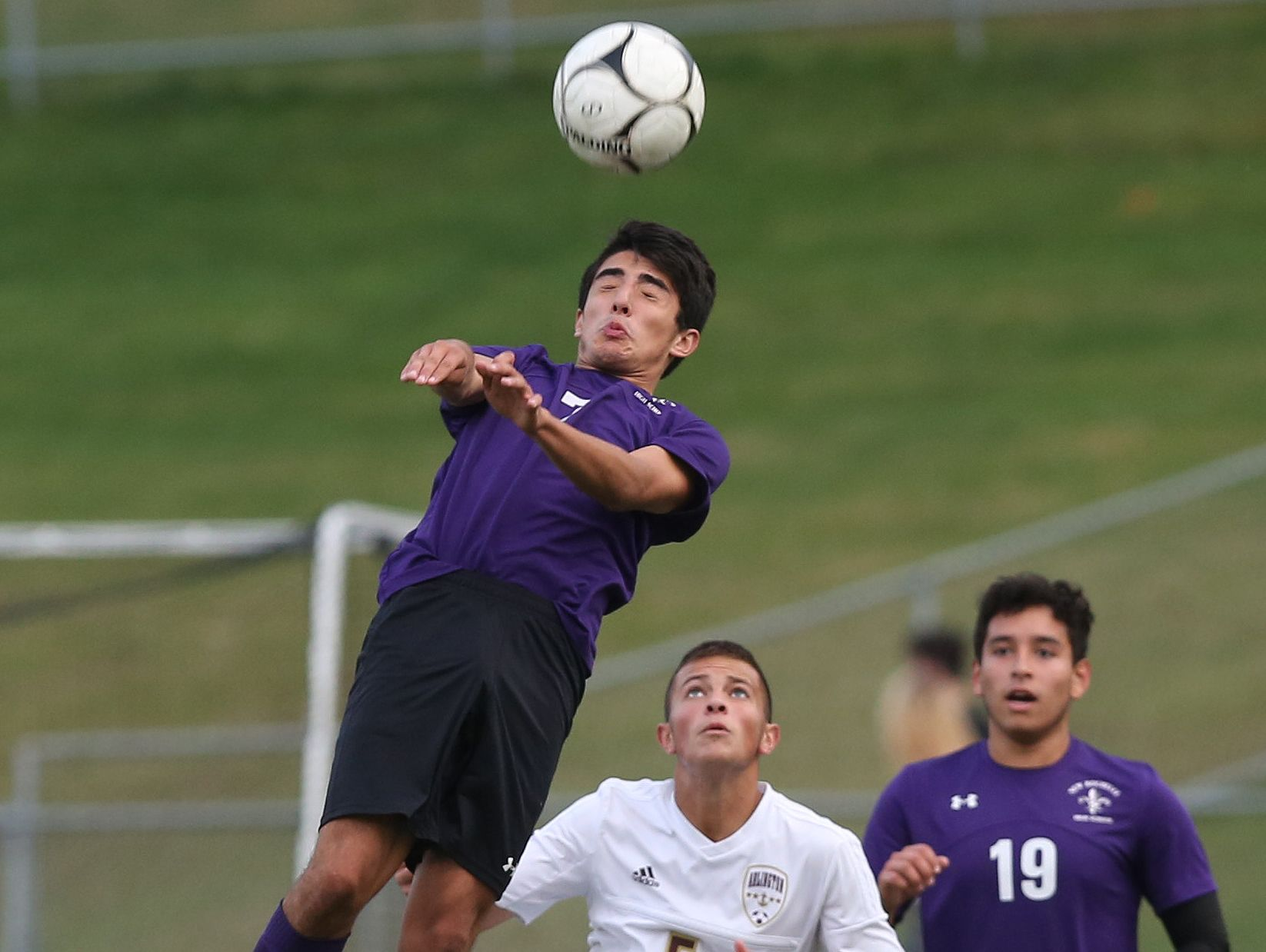 New Rochelle's Cristian Valencia (7) heads the ball away from Arlington's (5) during the boys soccer Section 1 Class AA championship game at Lakeland High School in Shrub Oak High School Oct. 29, 2016. Valencia had two goals in New Rochelle's 3-0 victory.